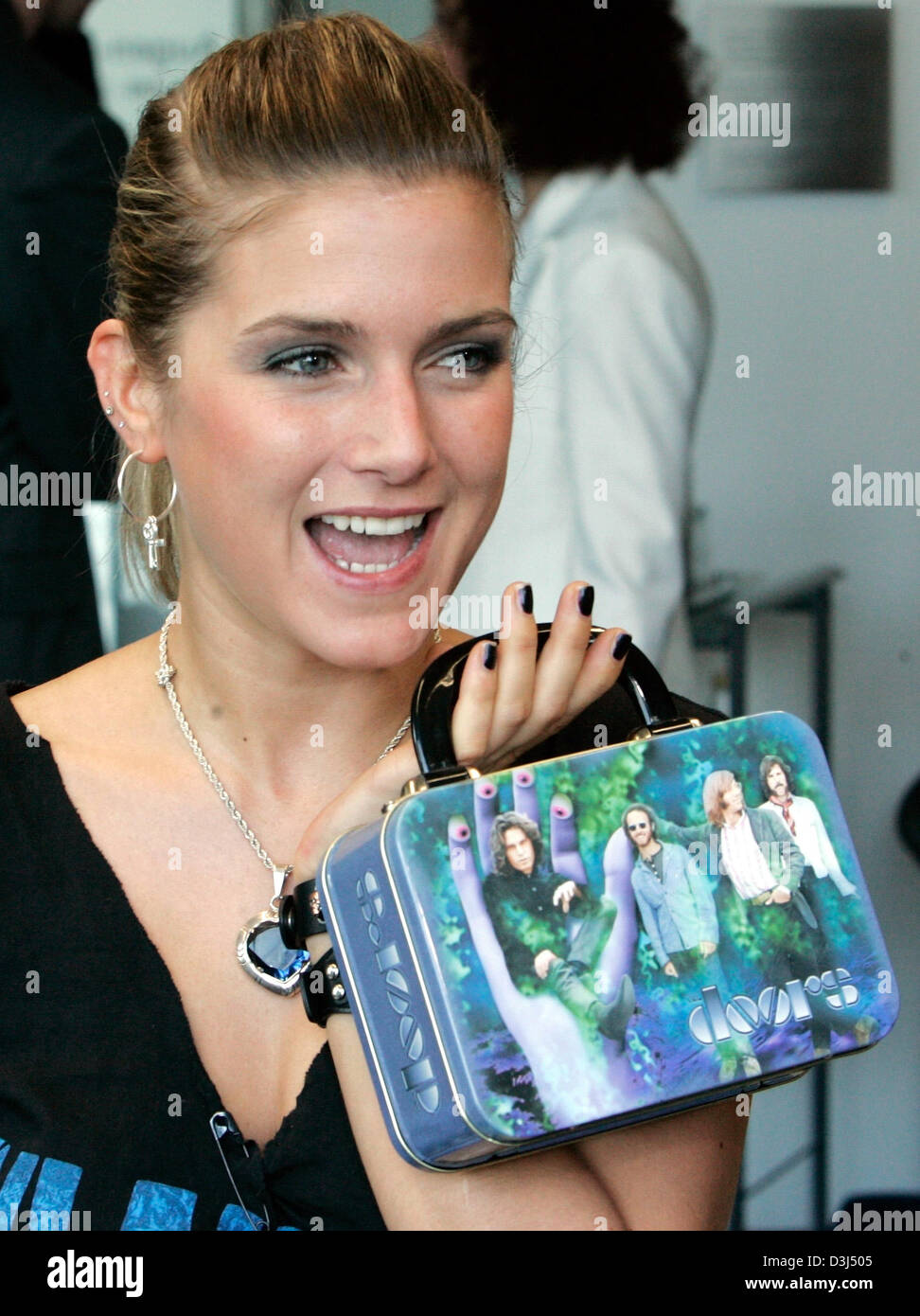 dpa german pop singer jeanette biedermann poses with a tiny suitcase prior to a press conference in berlin 03 june 2005 after her eye laser surgery in