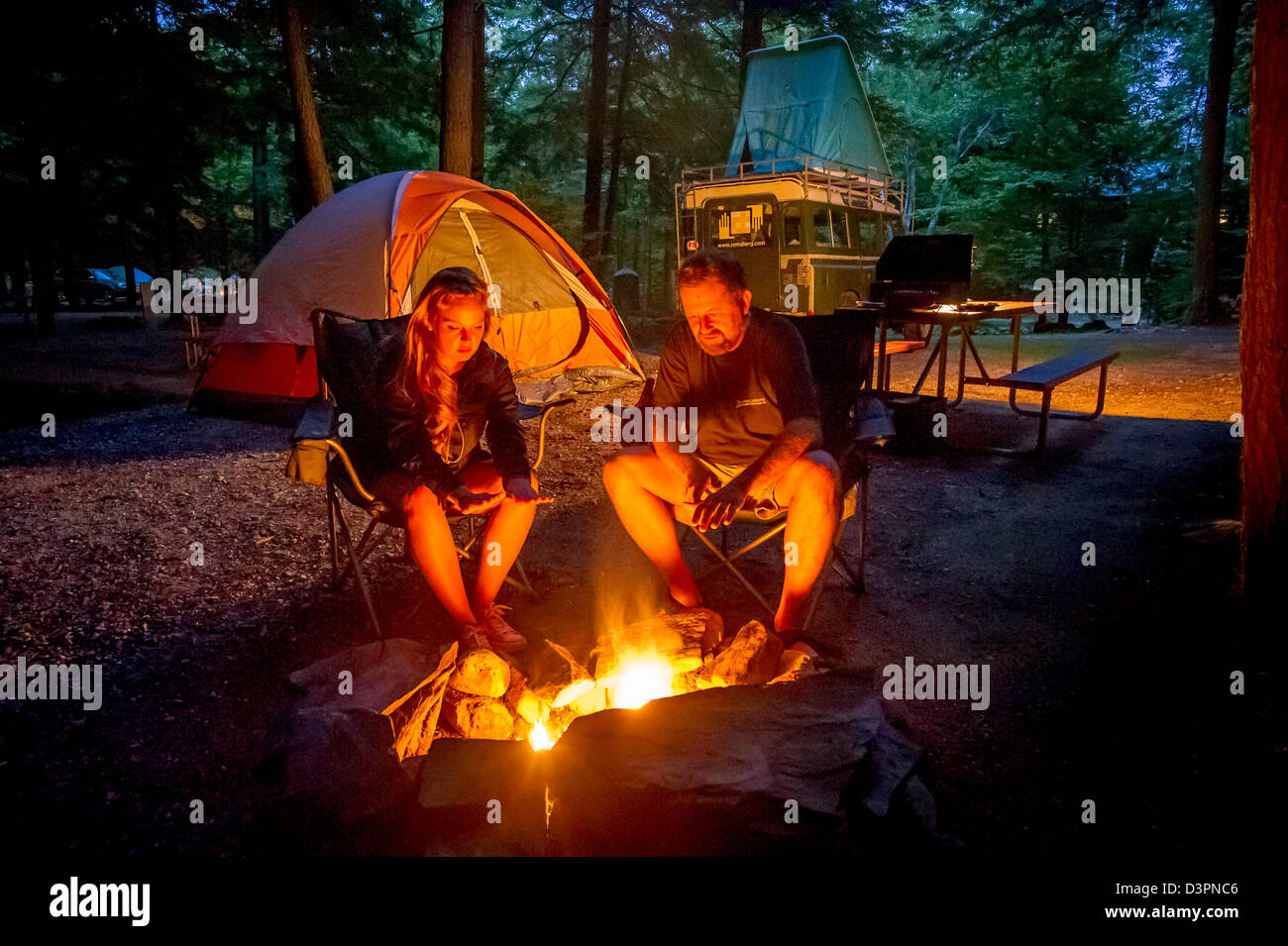 Couple by c&site fire with tents Sebago Lake Maine USA & Couple by campsite fire with tents Sebago Lake Maine USA Stock ...