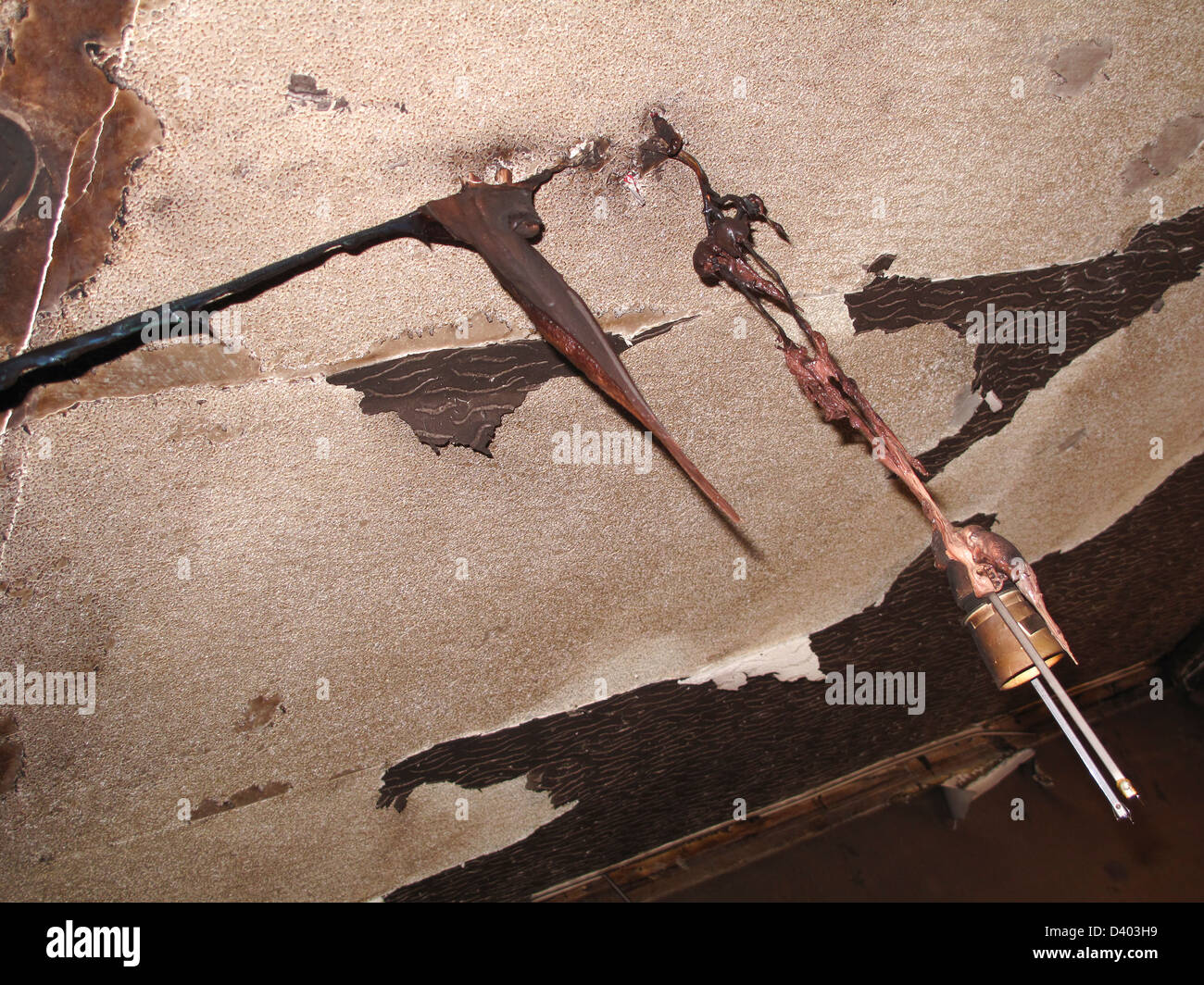 Melted light fitting and wiring in fire damaged house Stock Photo ...