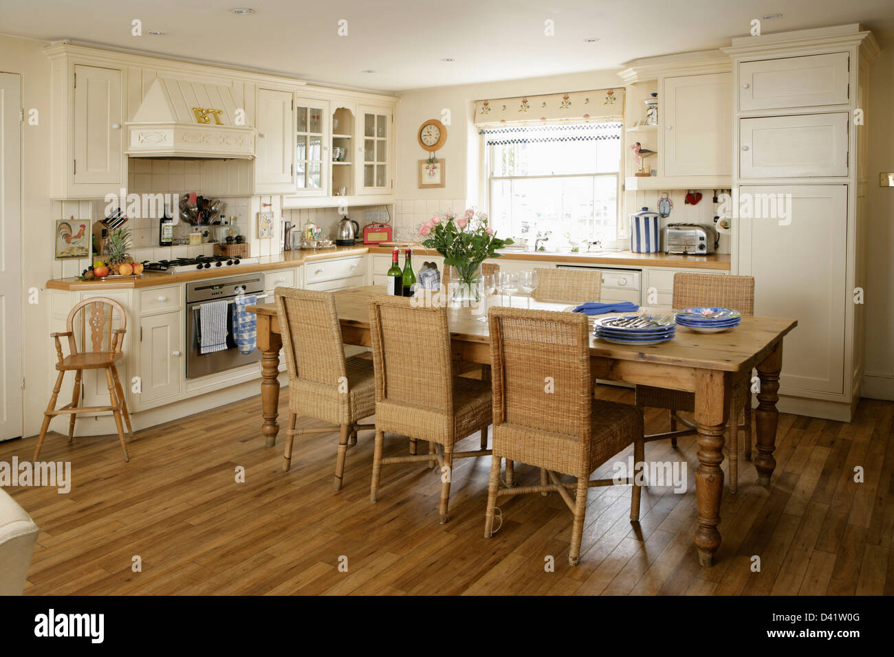 Tall country dining room sets - Stock Photo Tall Back Wicker Dining Chairs At Long Pine Table In Country Style Kitchen With Child S Wooden High Chair