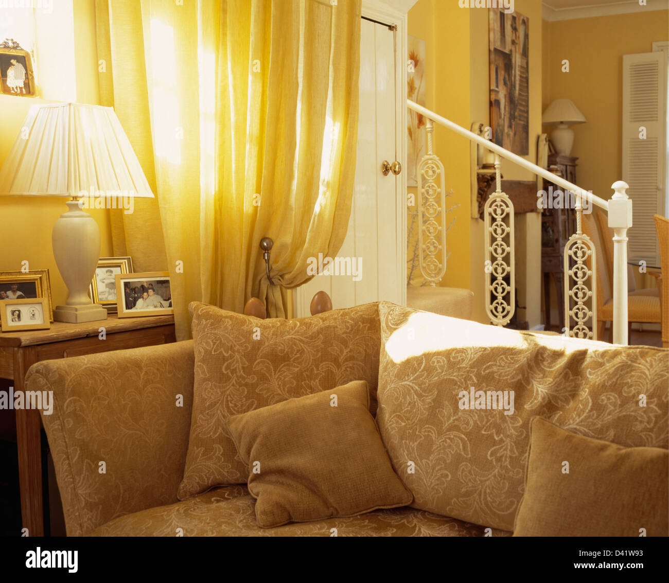 Pale Yellow Door Curtain Beside Beige Patterned Sofa With Matching Cushions In Front Of Painted Banister Living Room