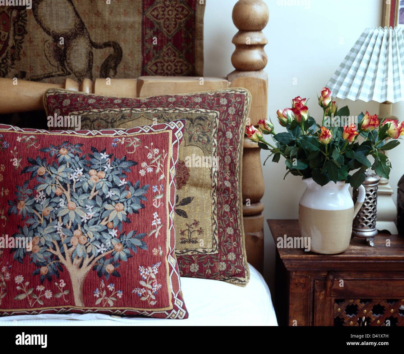Close-up of tapestry cushions on bed beside cabinet with jug of ...