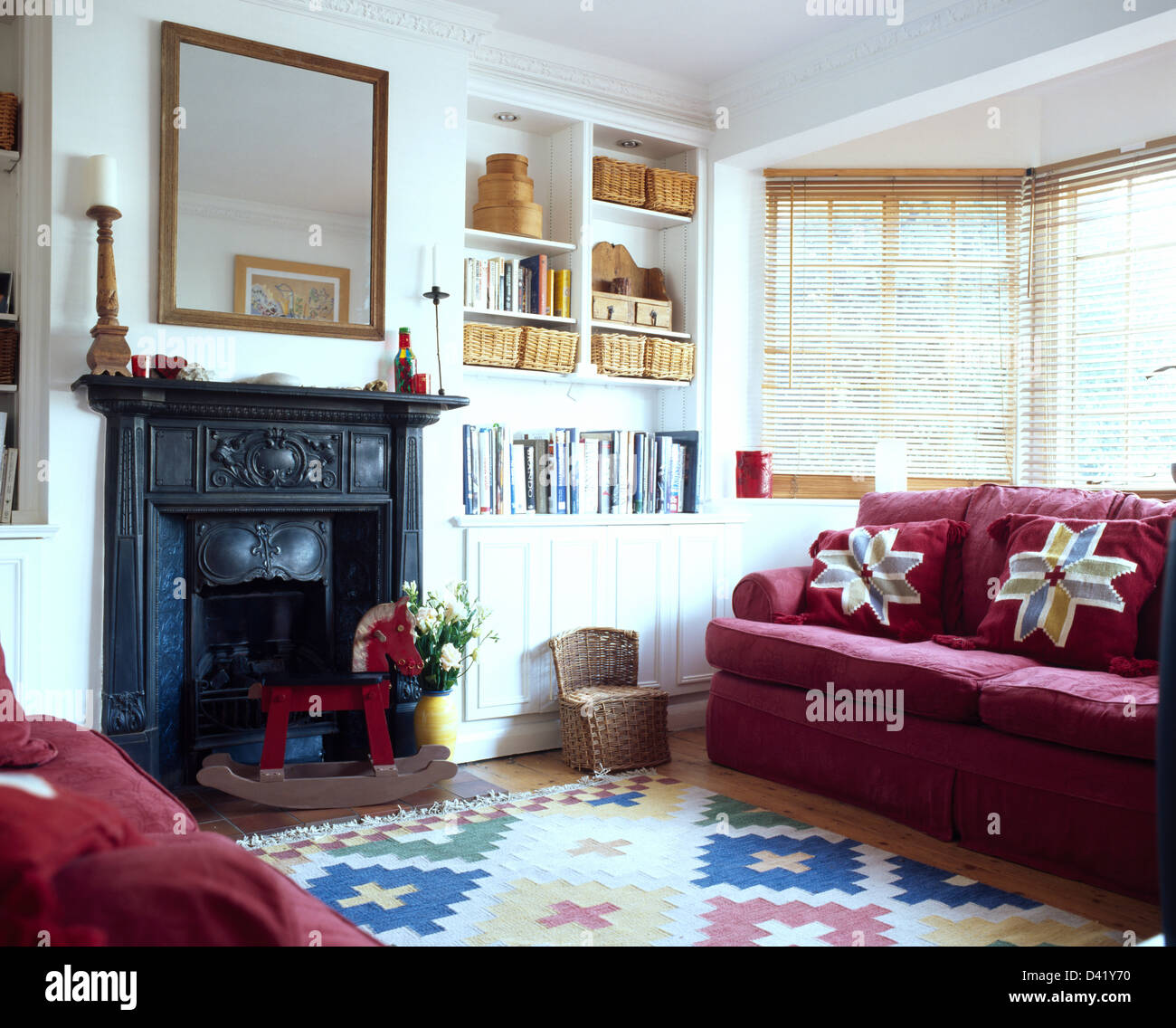 Red Sofas On Either Side Of Black Cast Iron Edwardian Fireplace In Sitting Room With Kelim