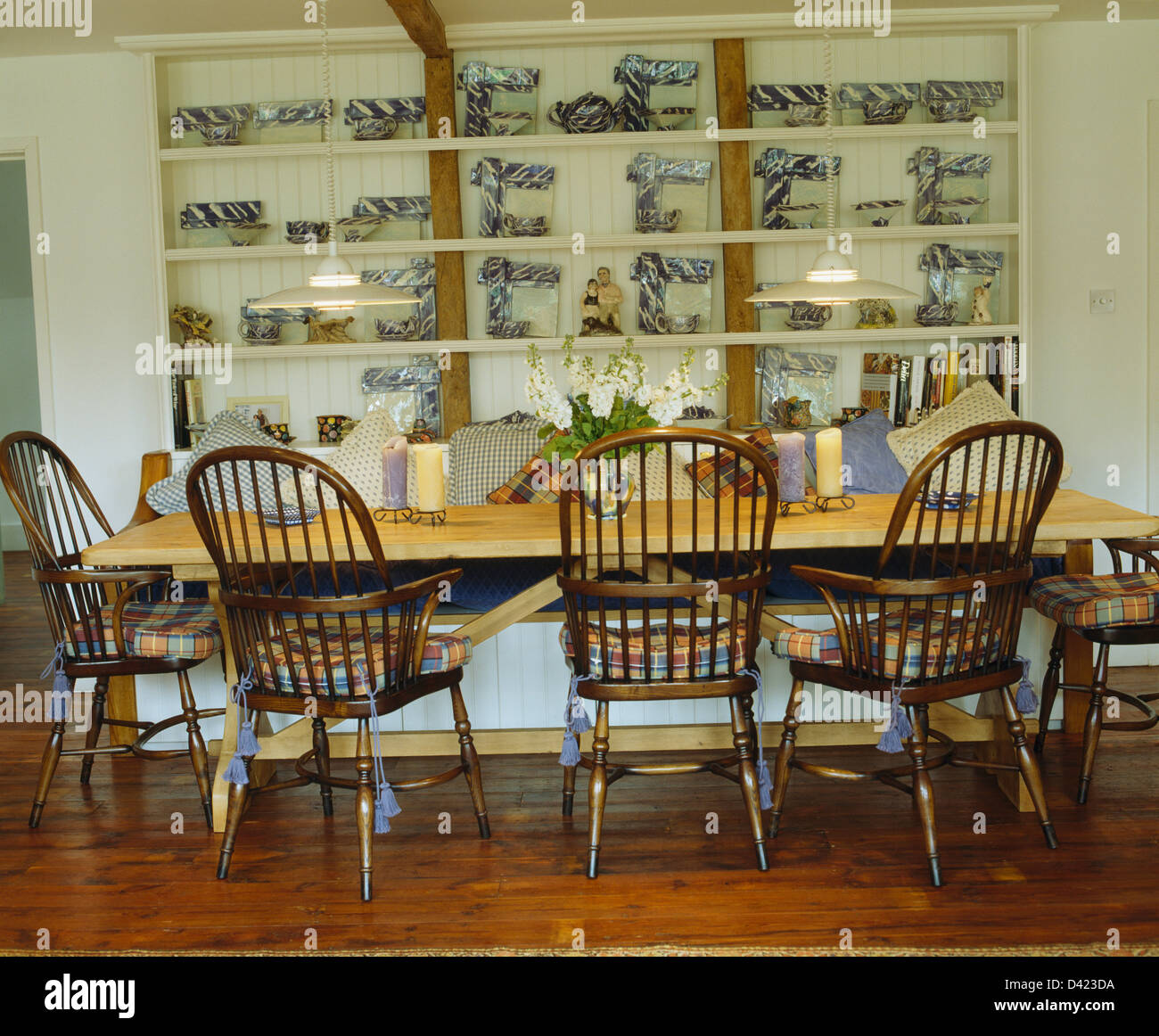 Antique Windsor Chairs And Simple Pine Table In Country Dining Room With  Blue+white China Frames On White Shelves