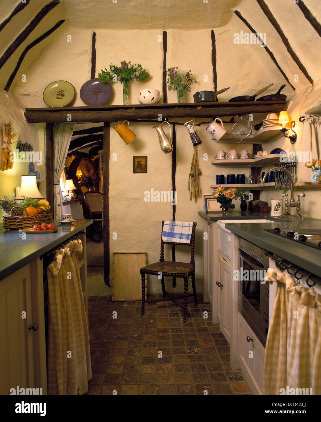 quarry tiled floor in small cottage kitchen with pitched ceiling