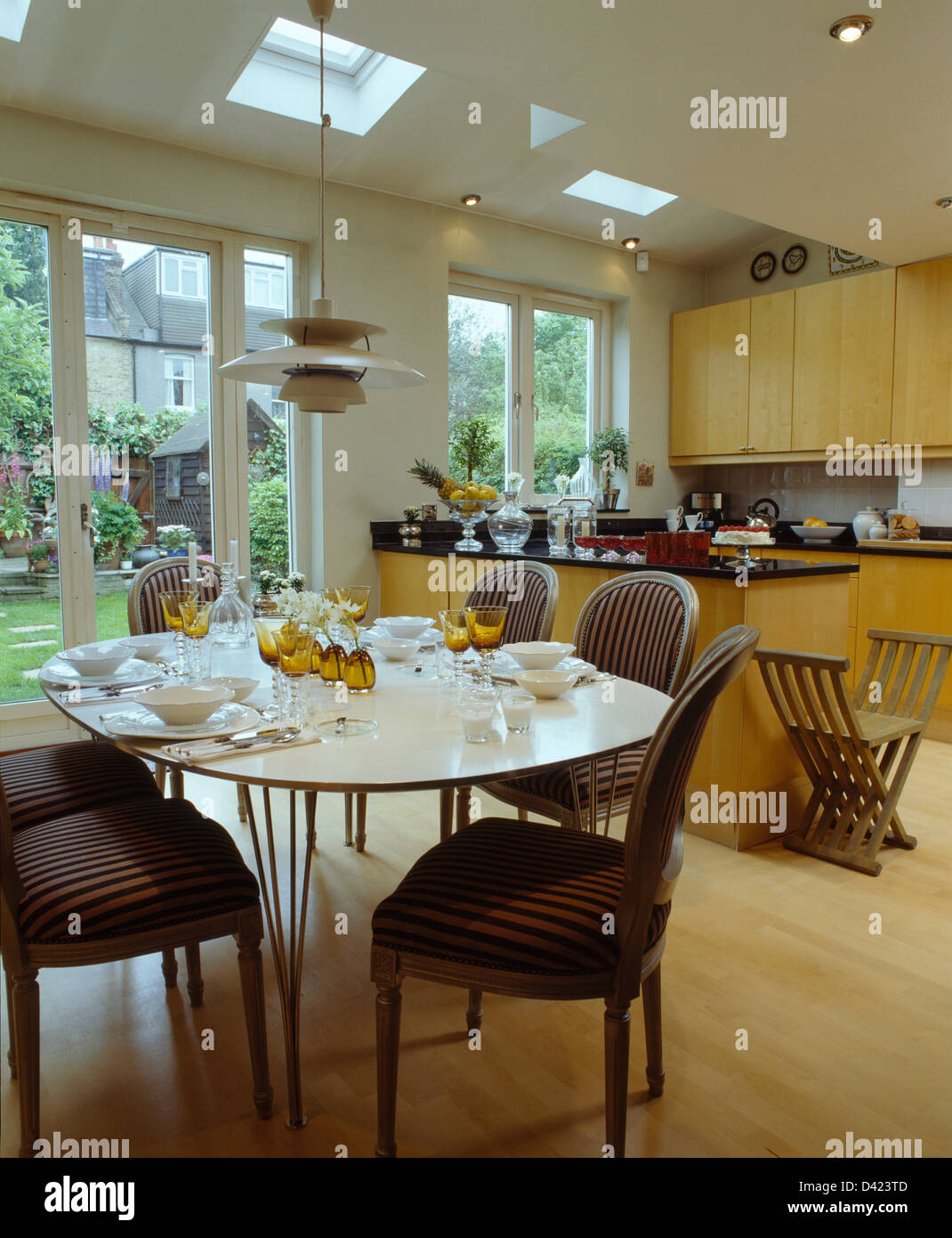 Stock Photo   Striped Upholstered Chairs At Oval White Table Set For Lunch  In Modern Kitchen Dining Room Extension With Wooden Flooring