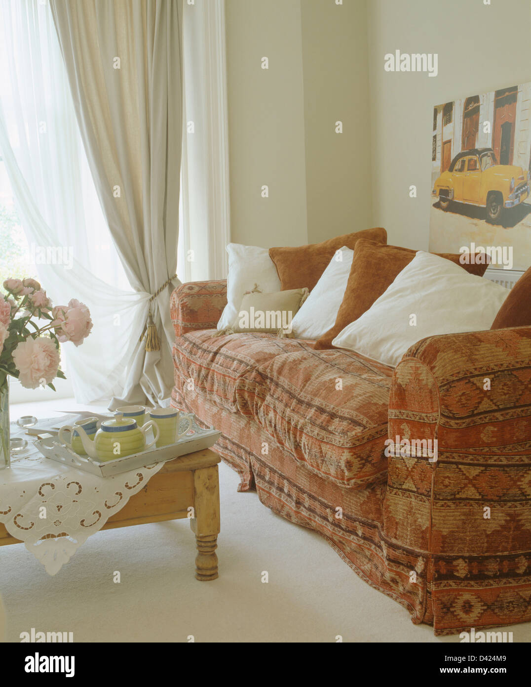 Red+brown patterned sofa with white cushions in townhouse living ...