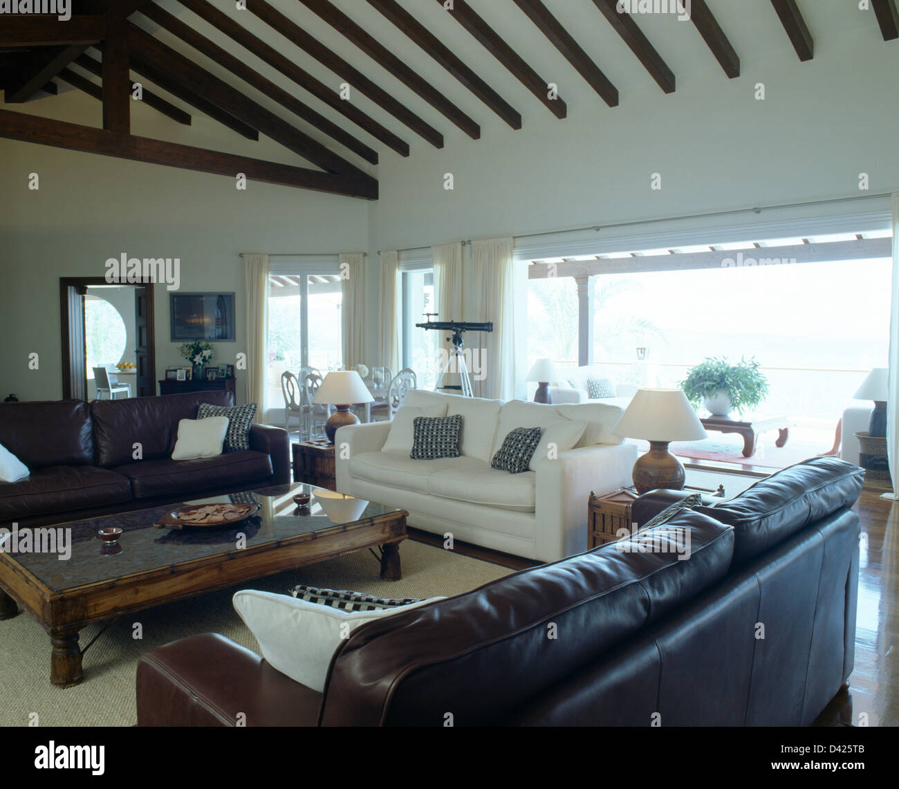 Coastal Living Rooms. Brown leather sofas and white sofa in modern coastal living room with  Indonesian wood coffee table beamed apex ceiling