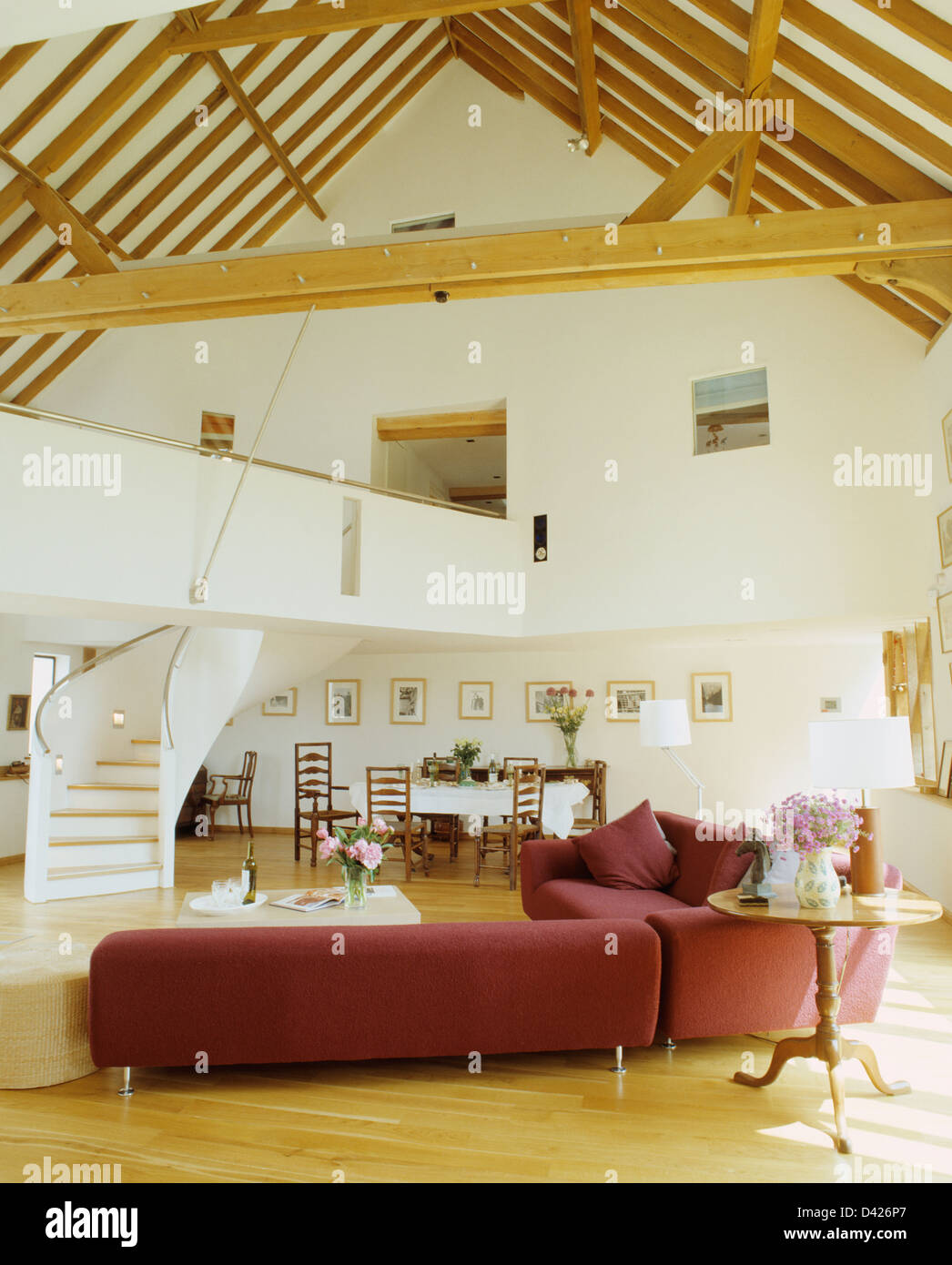 L Shaped Red Sofa And Wooden Flooring In Large Open Plan Living And Dining  Area In Barn Conversion With Beamed Apex Ceiling