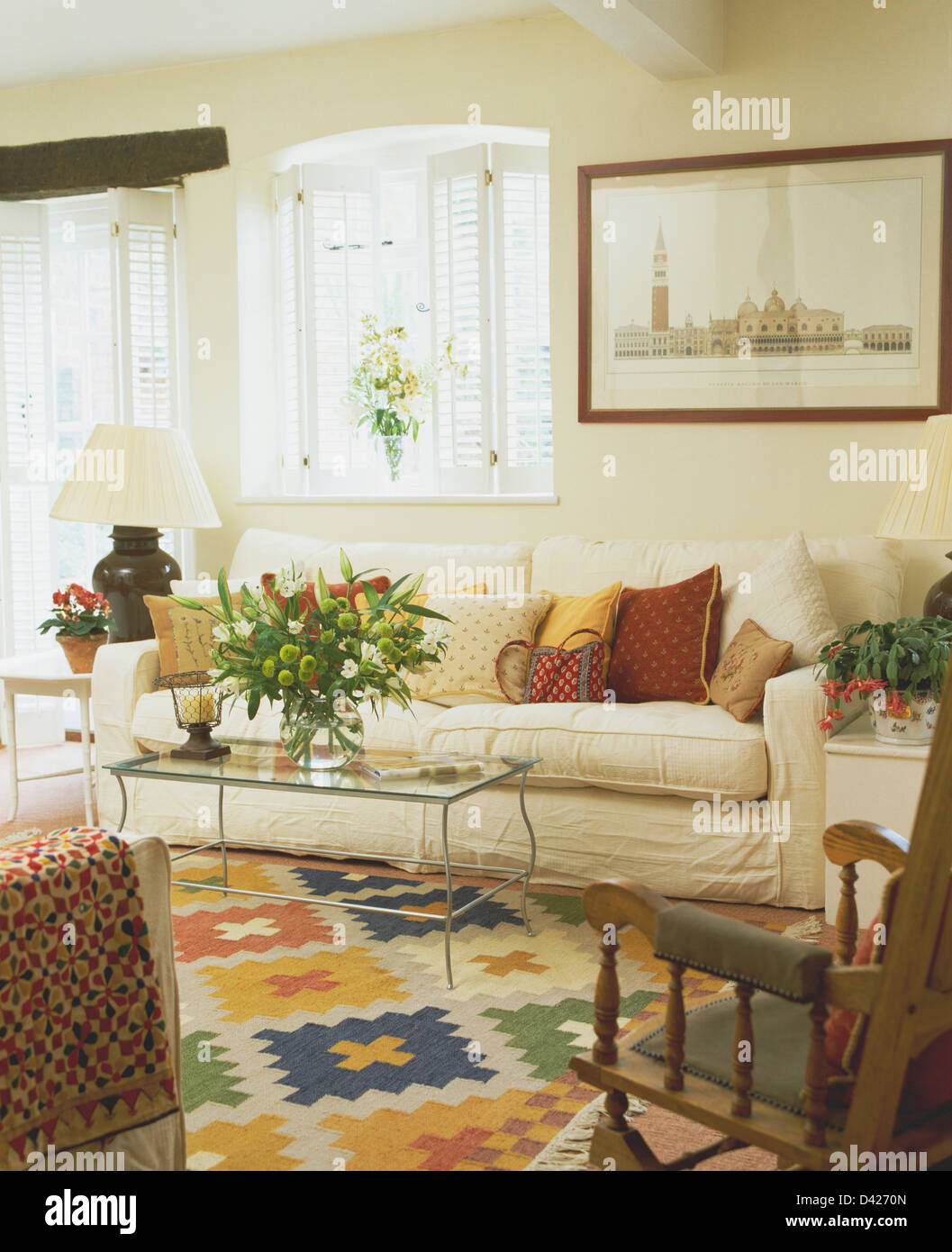 Stock Photo   White Plantation Shutters On Window Above Cream Sofa In  Cottage Living Room With Kelim Carpet And Glass Coffee Table