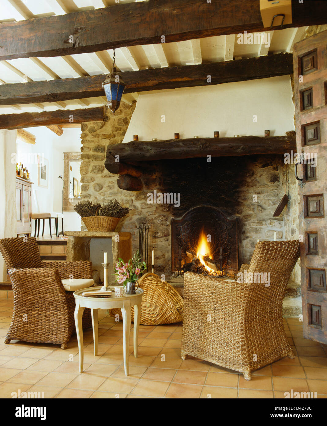 Small Country Living Rooms. Wicker armchairs and small table in French country living room with rustic  beamed ceiling fireplace lighted fire