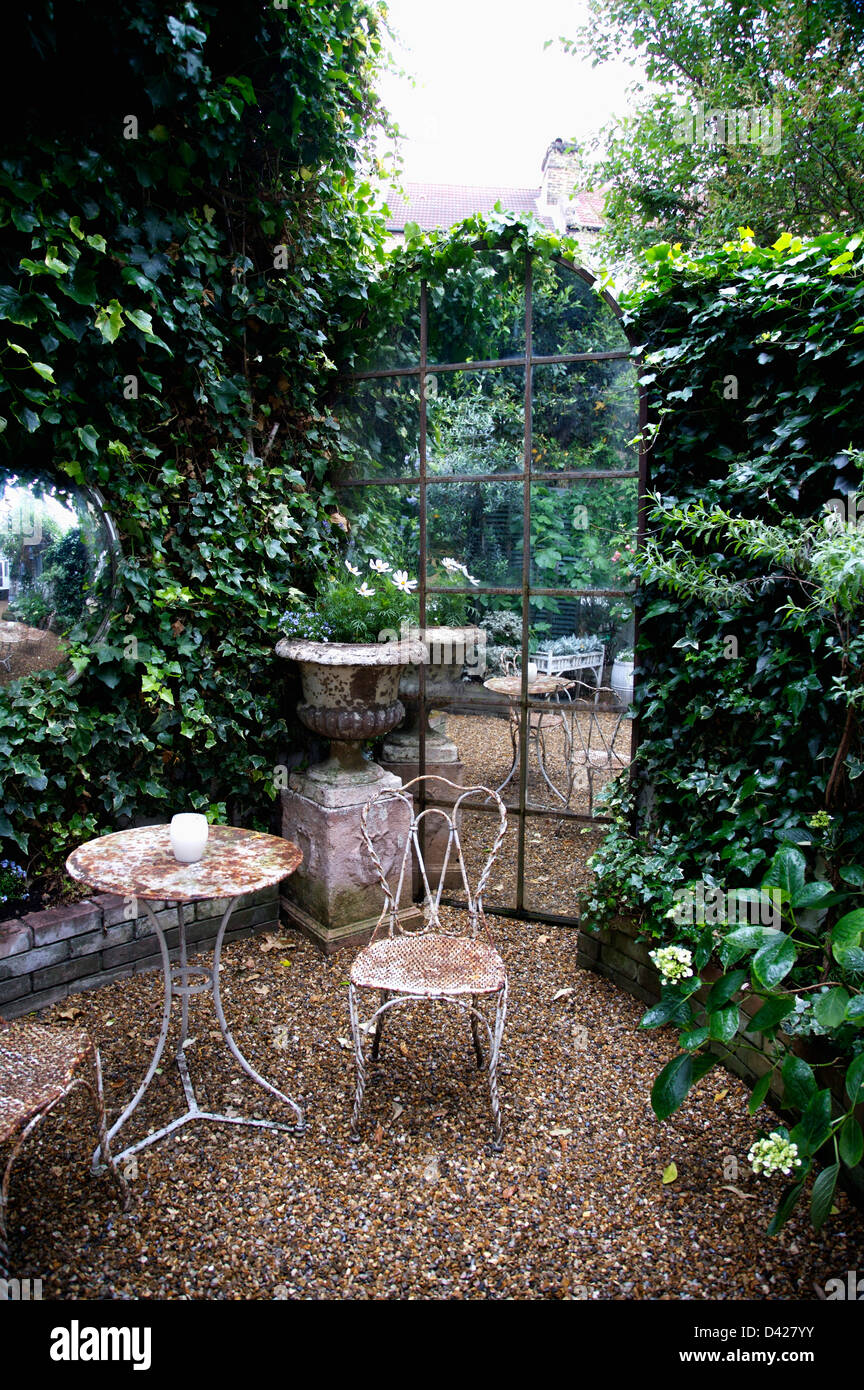 Old Metal Table And Chairs On Gravel In Front Of Arched Window Shaped Mirror  In Townhouse Garden With Ivy Covered Walls