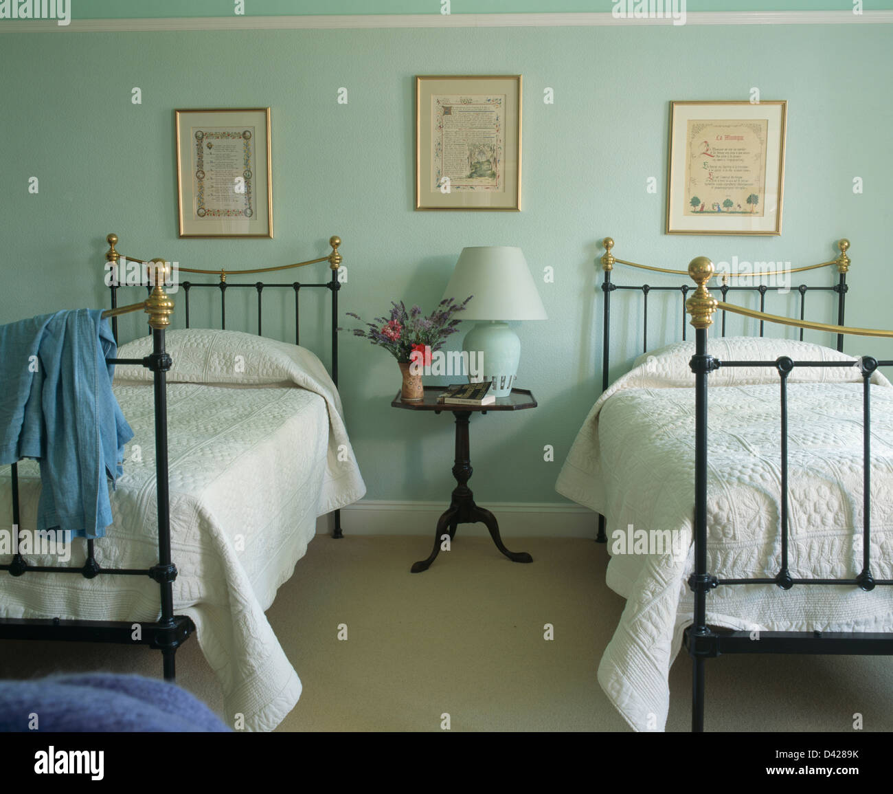white quilts on antique twin brass beds in pastel green french