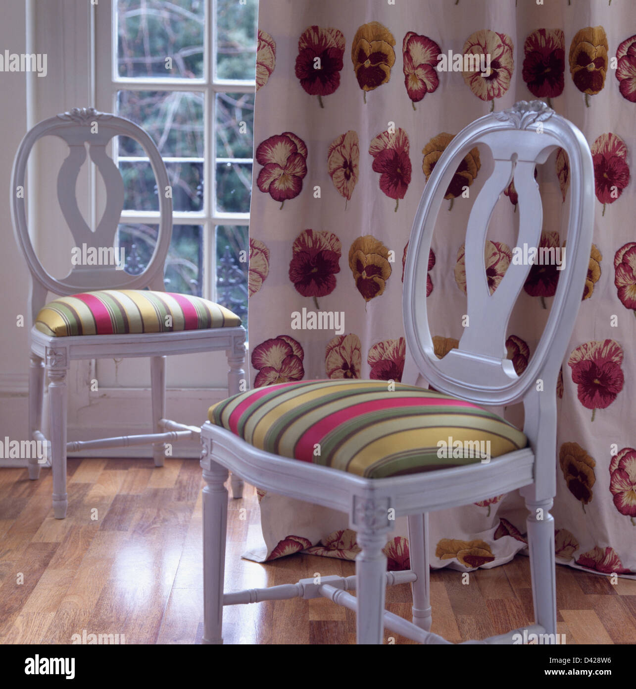 Colorful Striped Upholstered Seats On White French Style Dining Chairs  Against Pansy Patterned Curtain