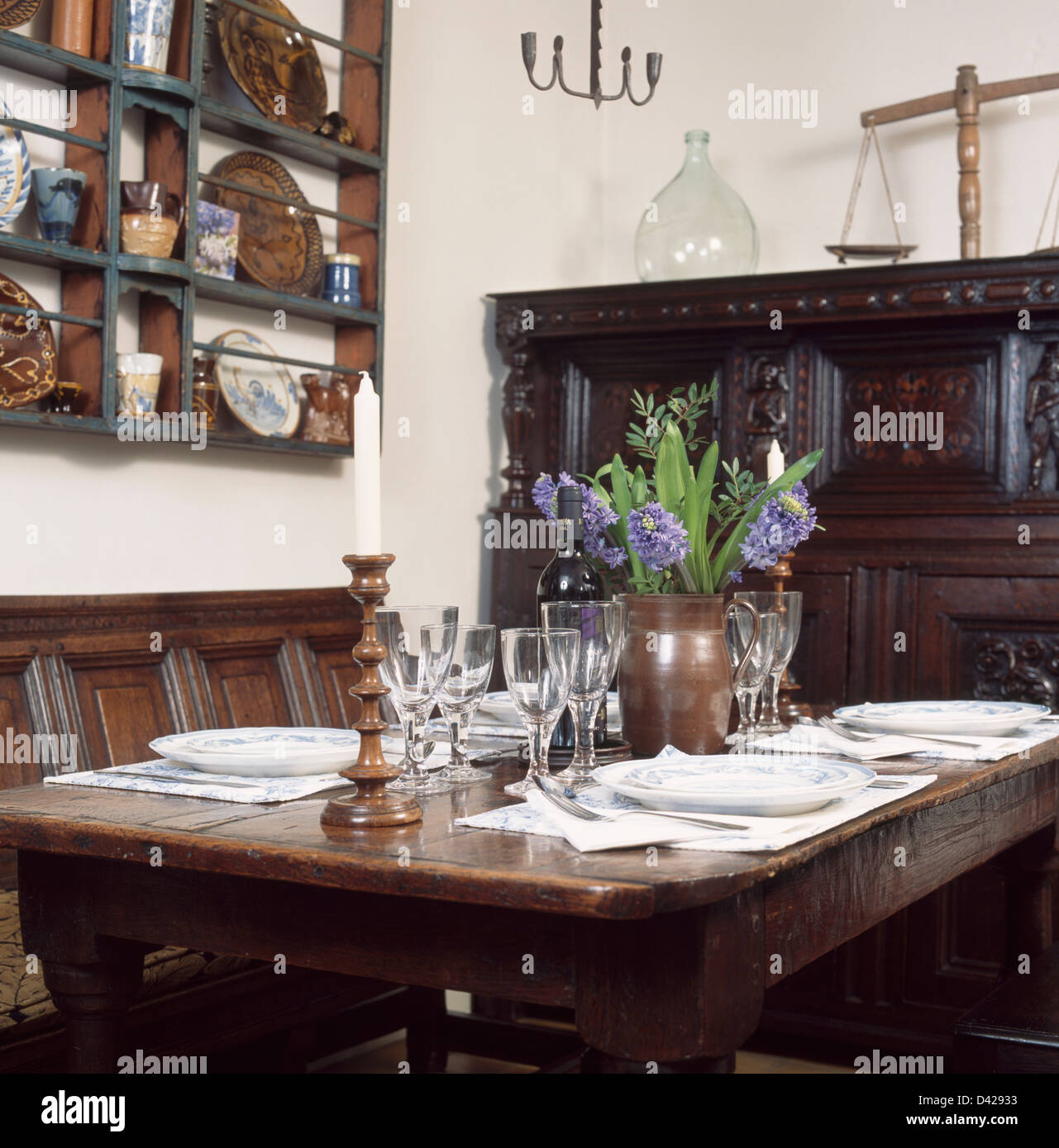 Oak Panelled Wall In Traditional Dining Room With Oak Settle And Glasses  And Place Settings On Table With Vase Of Blue Hyacinths