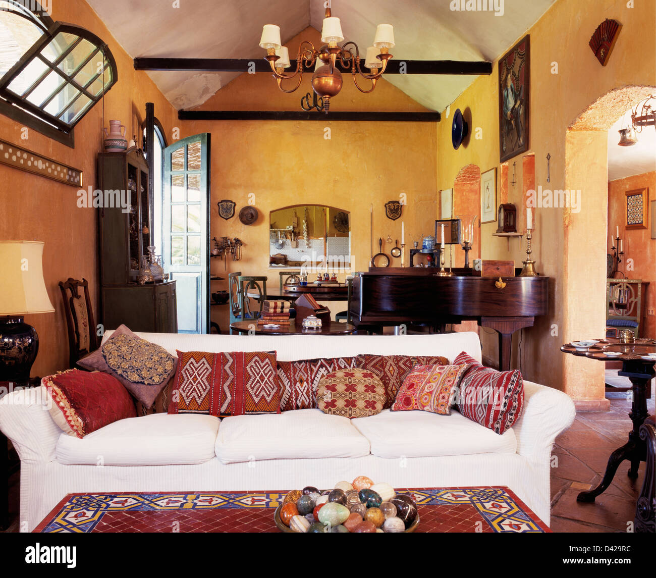White Sofa With Patterned Cushions In Yellow Spanish Living Room With Apex  Ceiling