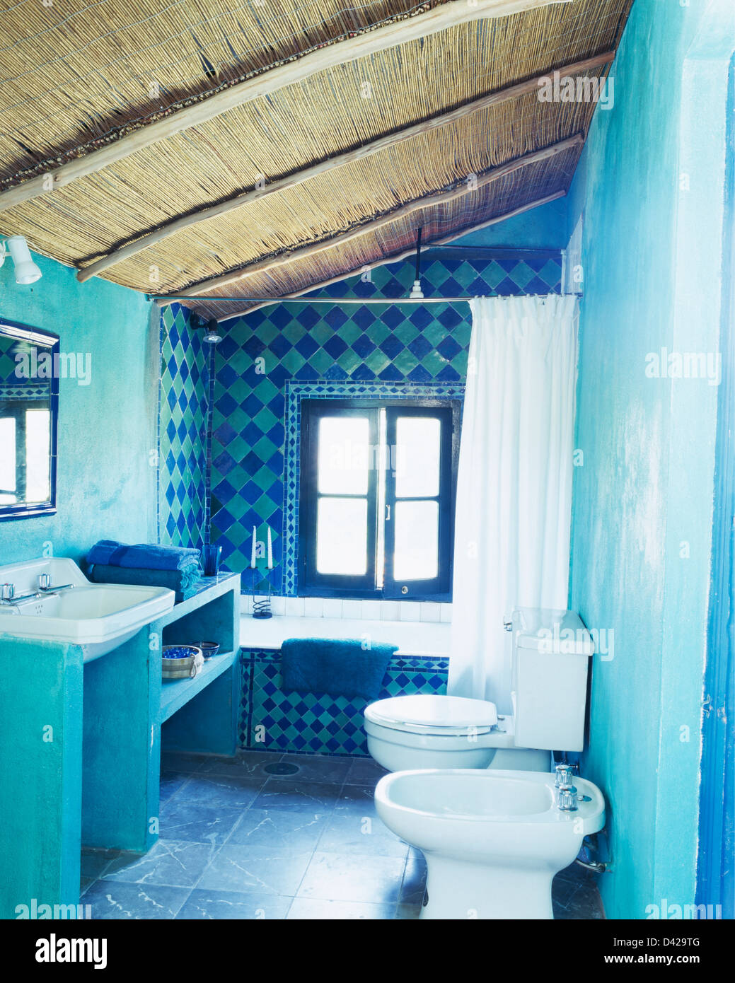 Thatched ceiling in turquoise Spanish bathroom with decorative ...