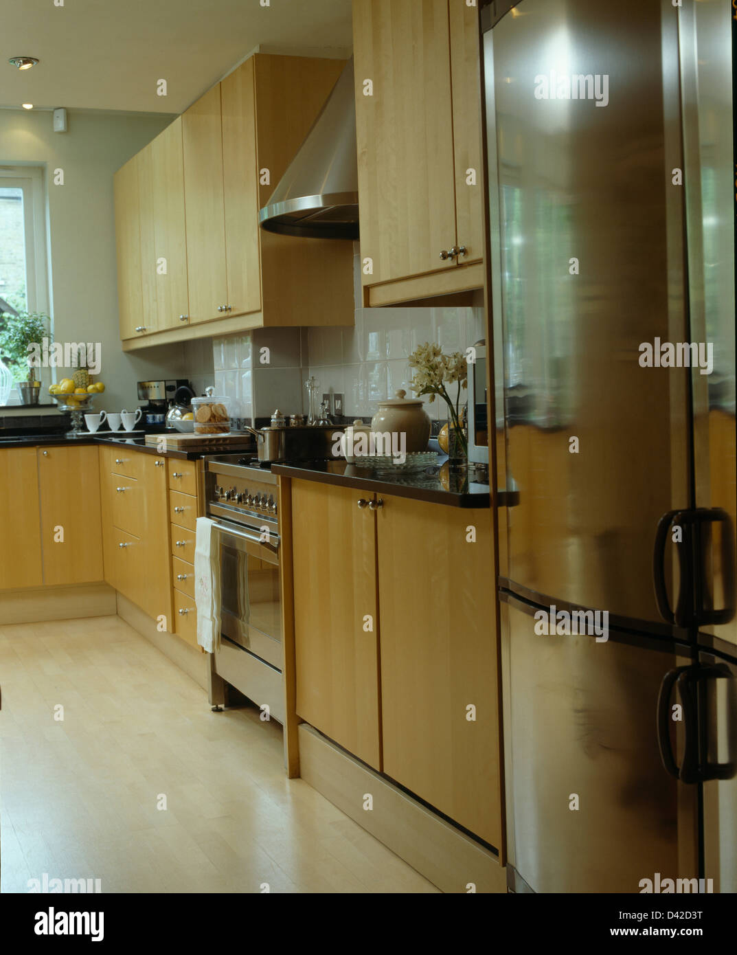 Stainless Steel Fridge Freezer In Modern Kitchen With Range Oven And Pale  Wood Fitted Units