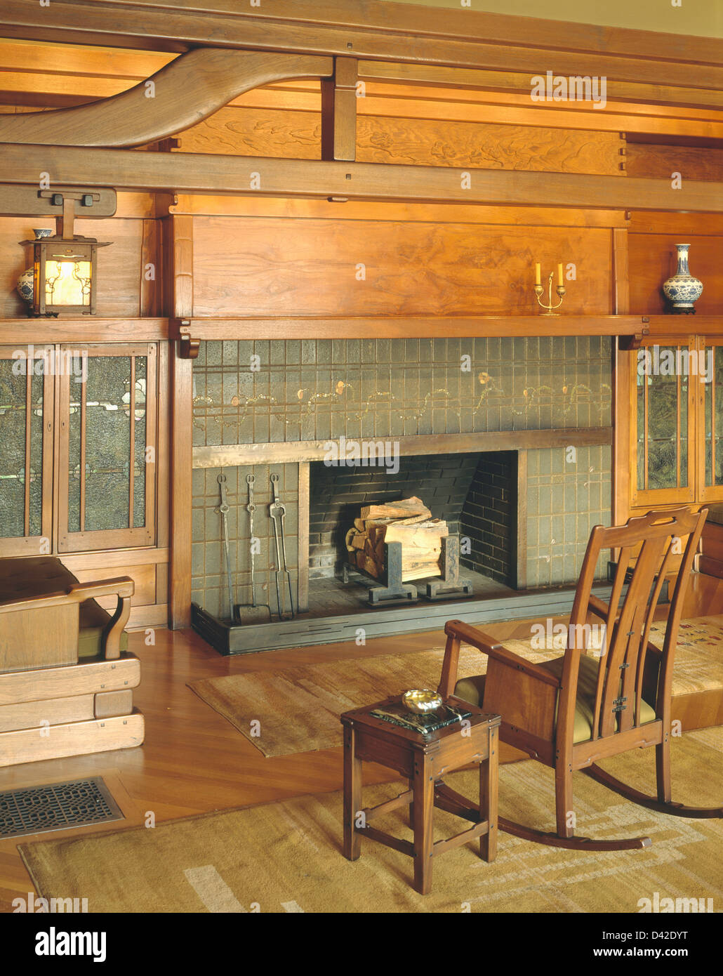 wooden table and rocking chair in front of fireplace in the gamble