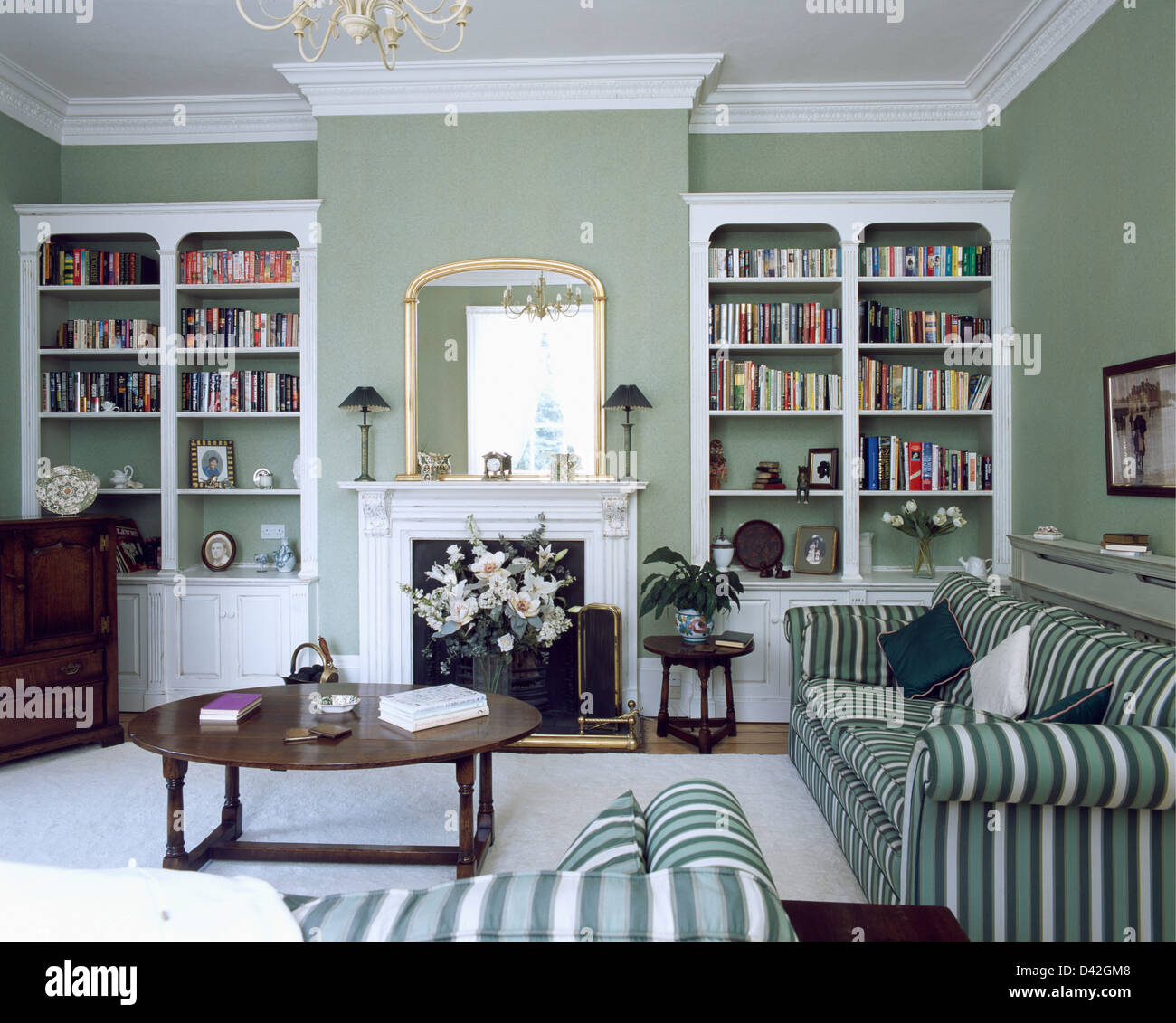 Fitted White Bookcases On Either Side Of Fireplace In Gray Green Living Room With