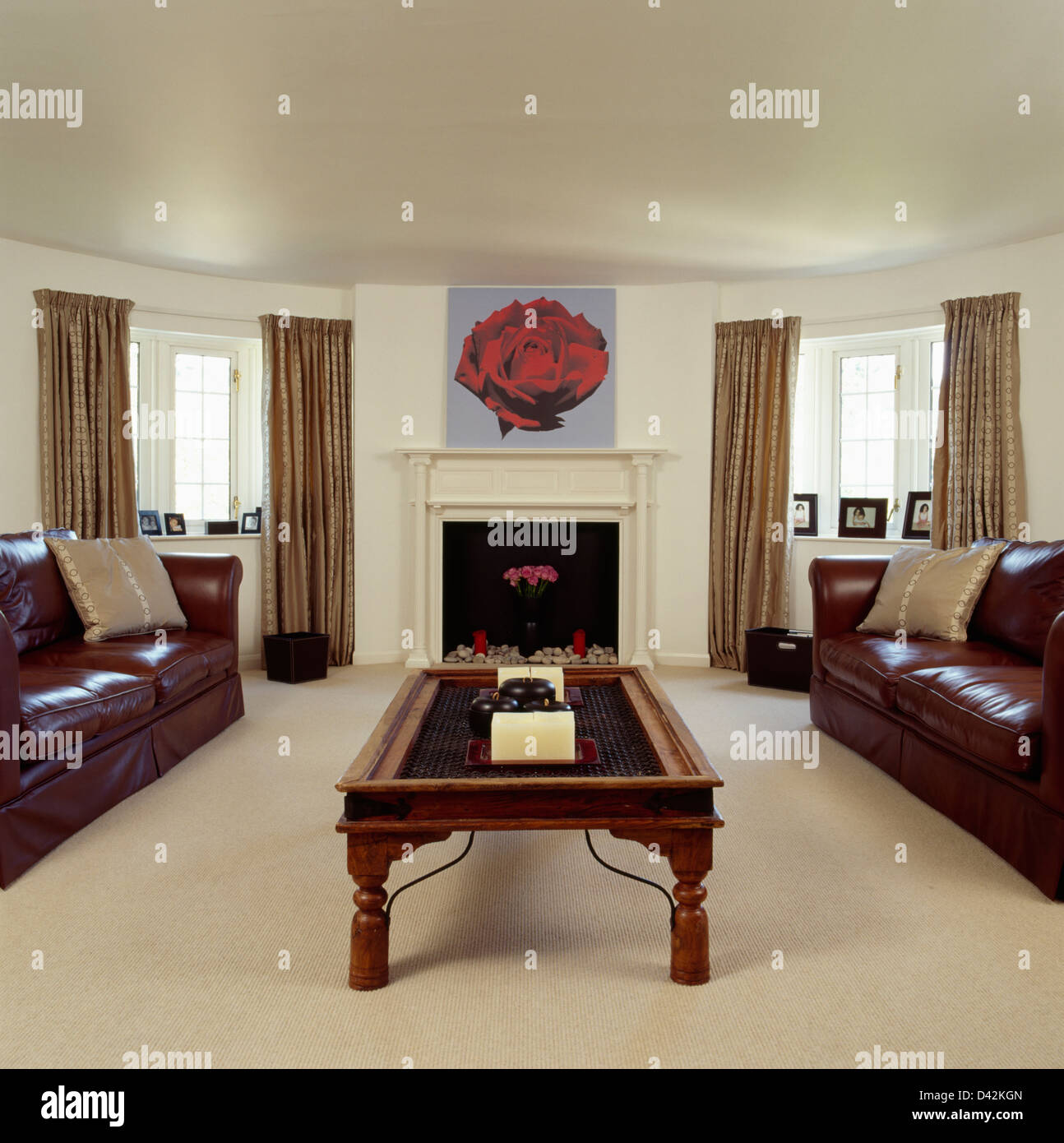 Carpet In Living Room. Brown leather sofa and Indonesian wood coffee table in living room with  cream carpet picture of red rose above fireplace