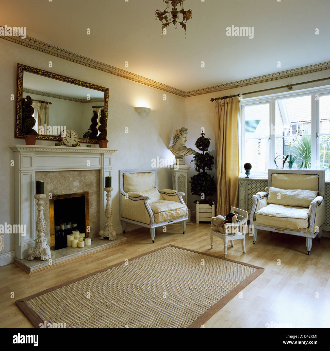 Mirror above fireplace with artificial topiary tree in living room