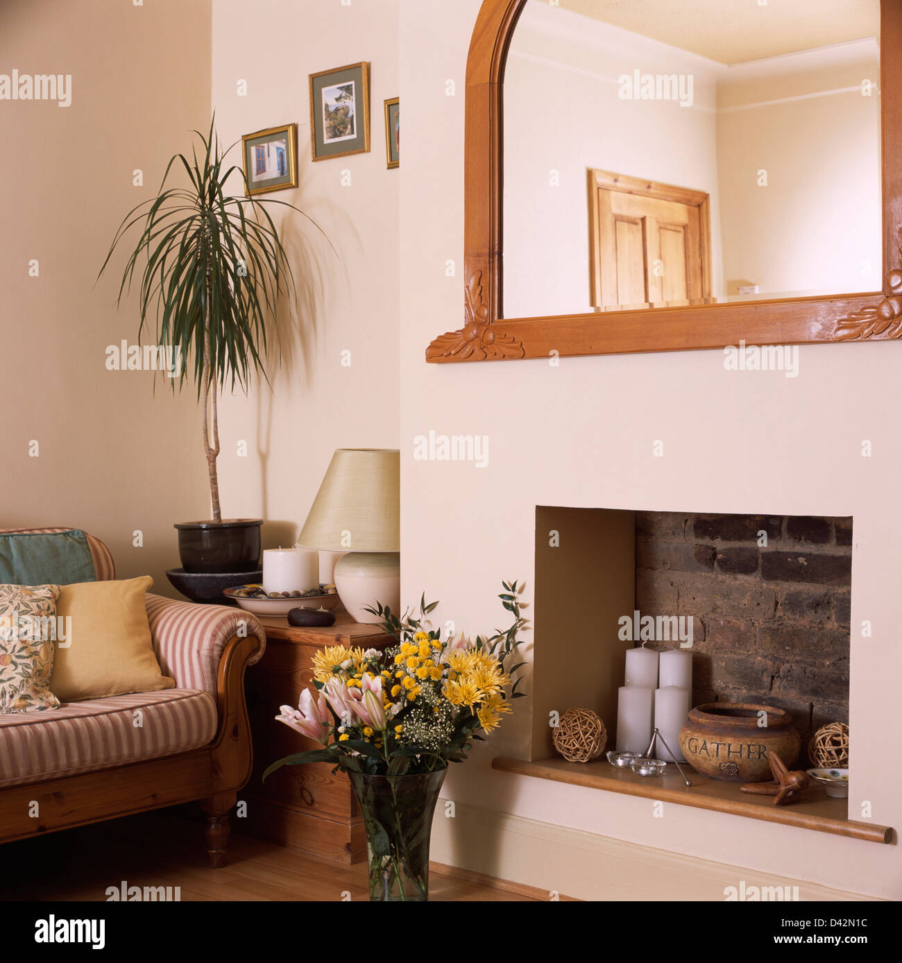 Mirror above simple fireplace alcove with candles in economy style ...