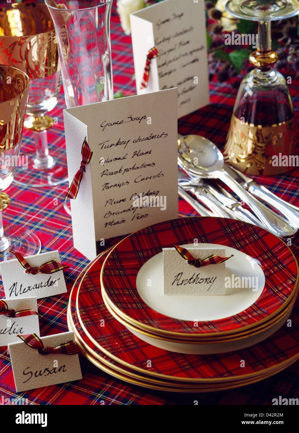 Table Set For Christmas Dinner pile of red tartan-edged plates on table set for christmas dinner