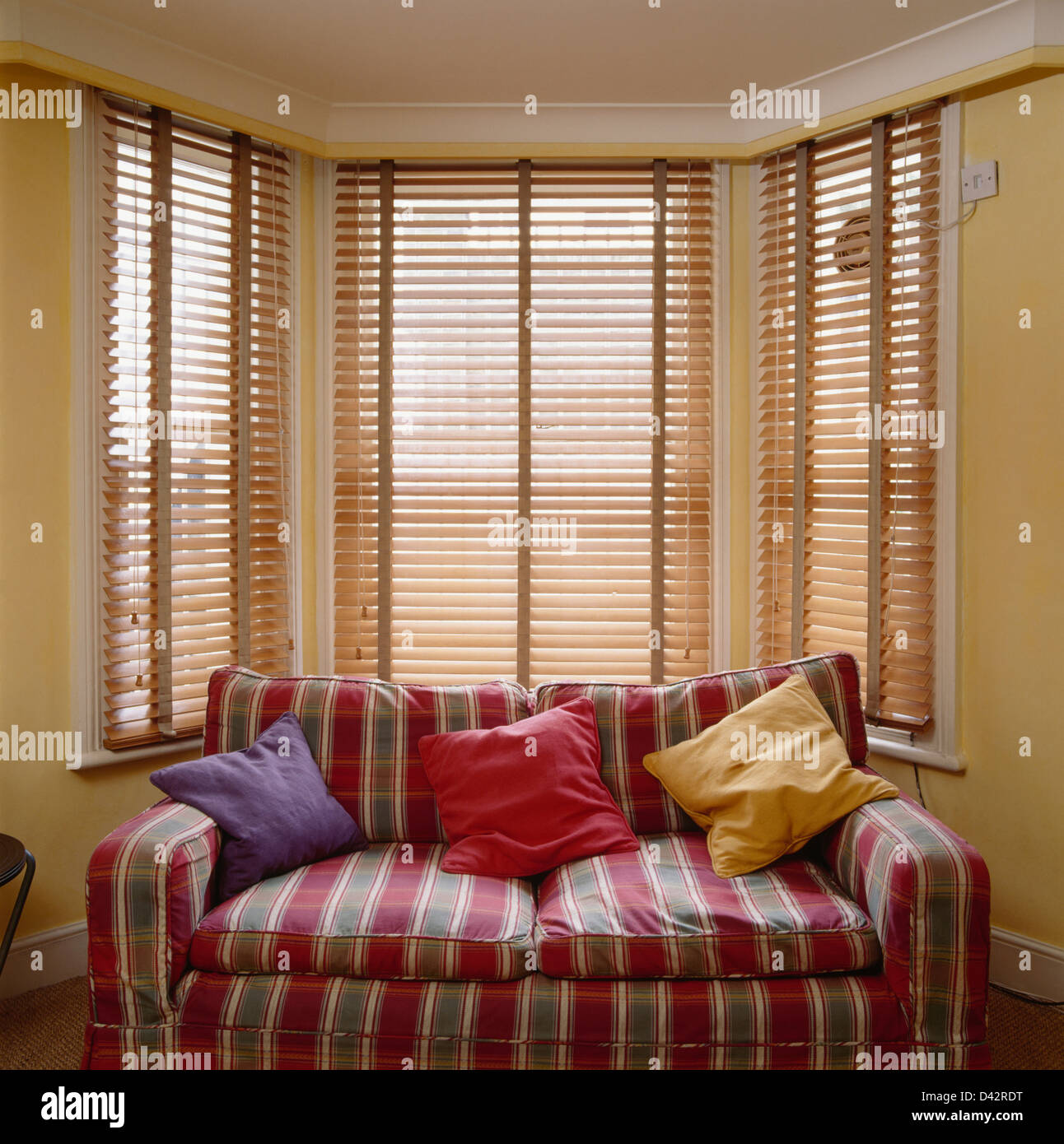 Cushions On Sofa With Red Striped Loose Cover In Front Of Bay Window With  Wooden Venetian Blind
