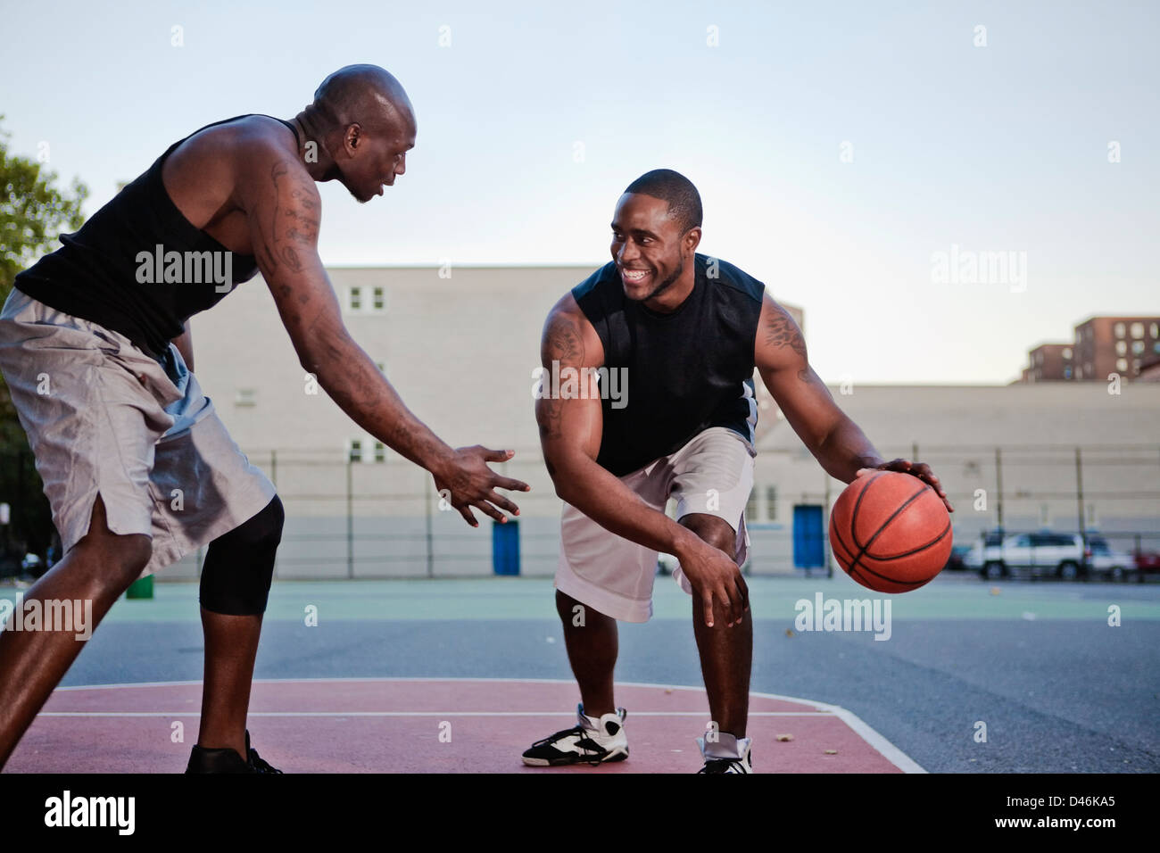 two young black men playing basketball after work stock photo