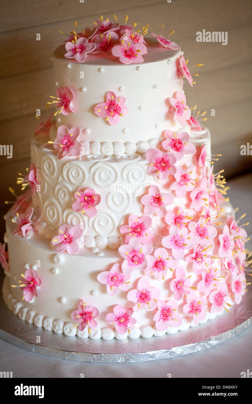 A White Three Tier Wedding Cake Decorated With Fuchsia Flowers