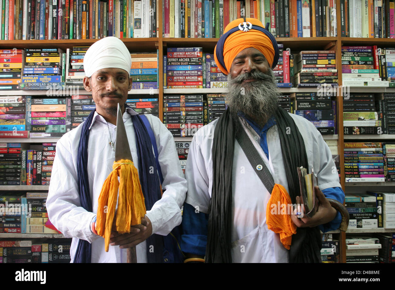 a sikh guru and his assistant collect alms in a book shop in new stock photo royalty free image. Black Bedroom Furniture Sets. Home Design Ideas