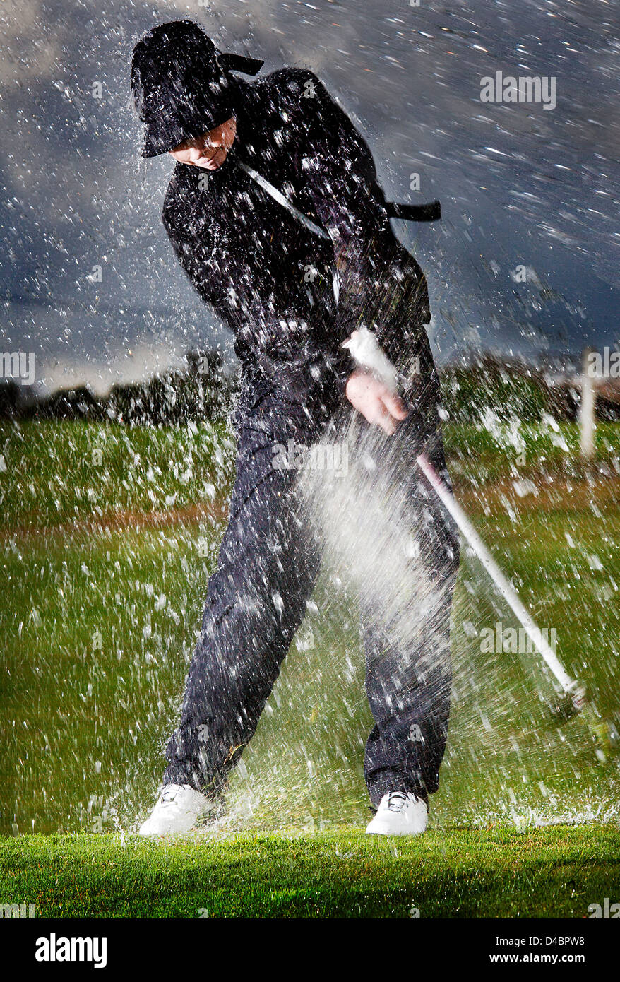 A European Male Age 20 25 Playing Golf In The Rain Stock
