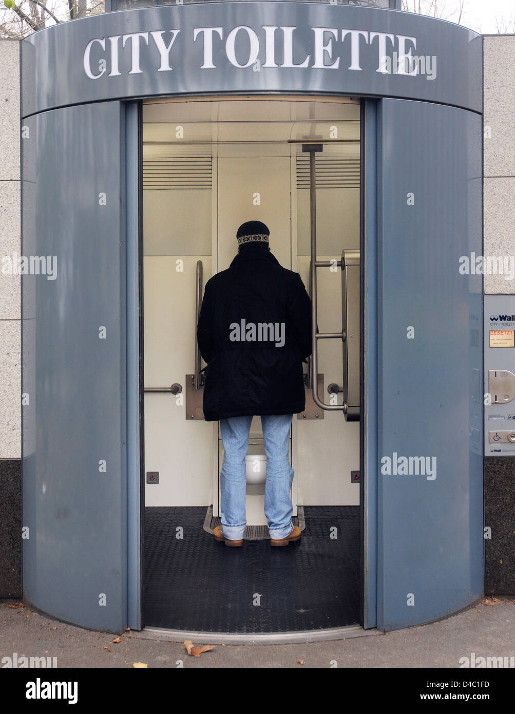 a man peeing in an open public lavatory in berlin germany. Black Bedroom Furniture Sets. Home Design Ideas