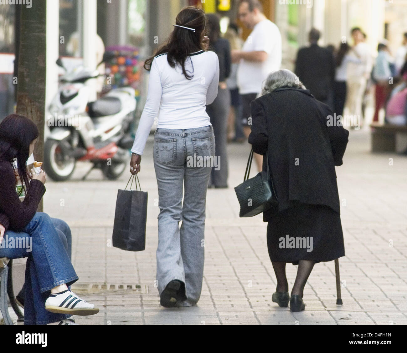 Symbolic a young and an old woman stooped over her walking cane symbolic a young and an old woman stooped over her walking cane walk next to each other at the pedestrian area in hamburg germany 26 april 2008 biocorpaavc Image collections