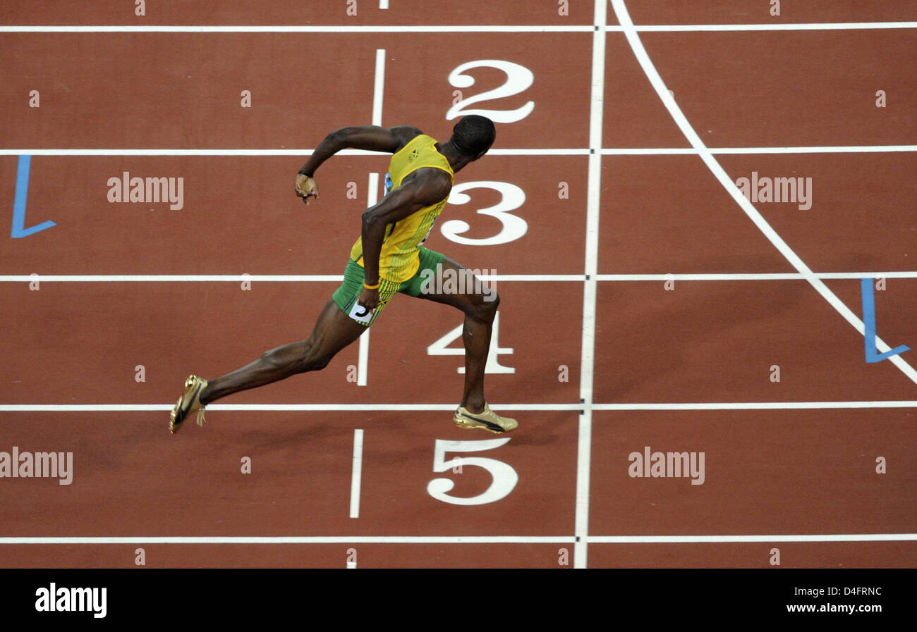 Usain Bolt From Jamaica Crosses The Finish Line To Place First In ...