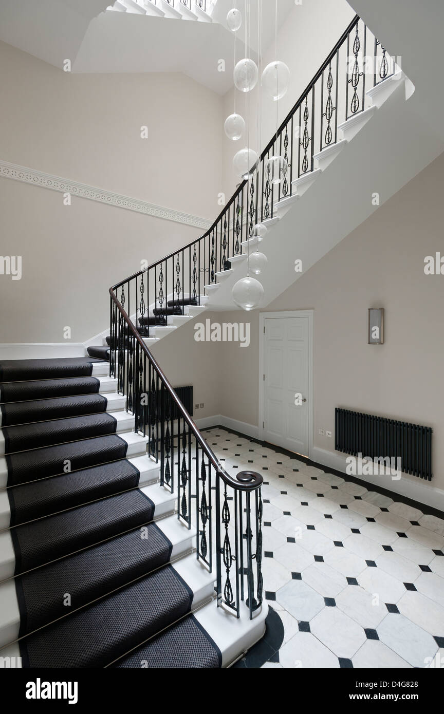 Entrance hall with staircase and black and white tiled floor stock entrance hall with staircase and black and white tiled floor dailygadgetfo Images