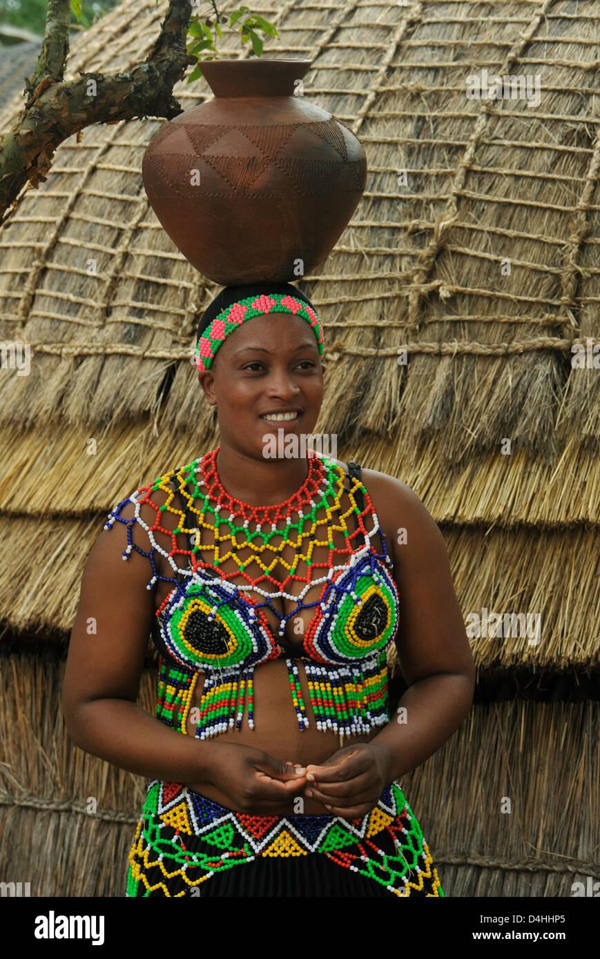 Zulu traditional dress in zulu kraal kwazulu natal - Zulu Maiden In Colourful Traditional Dress With Clay Pot On Head Next To Grass Hut At