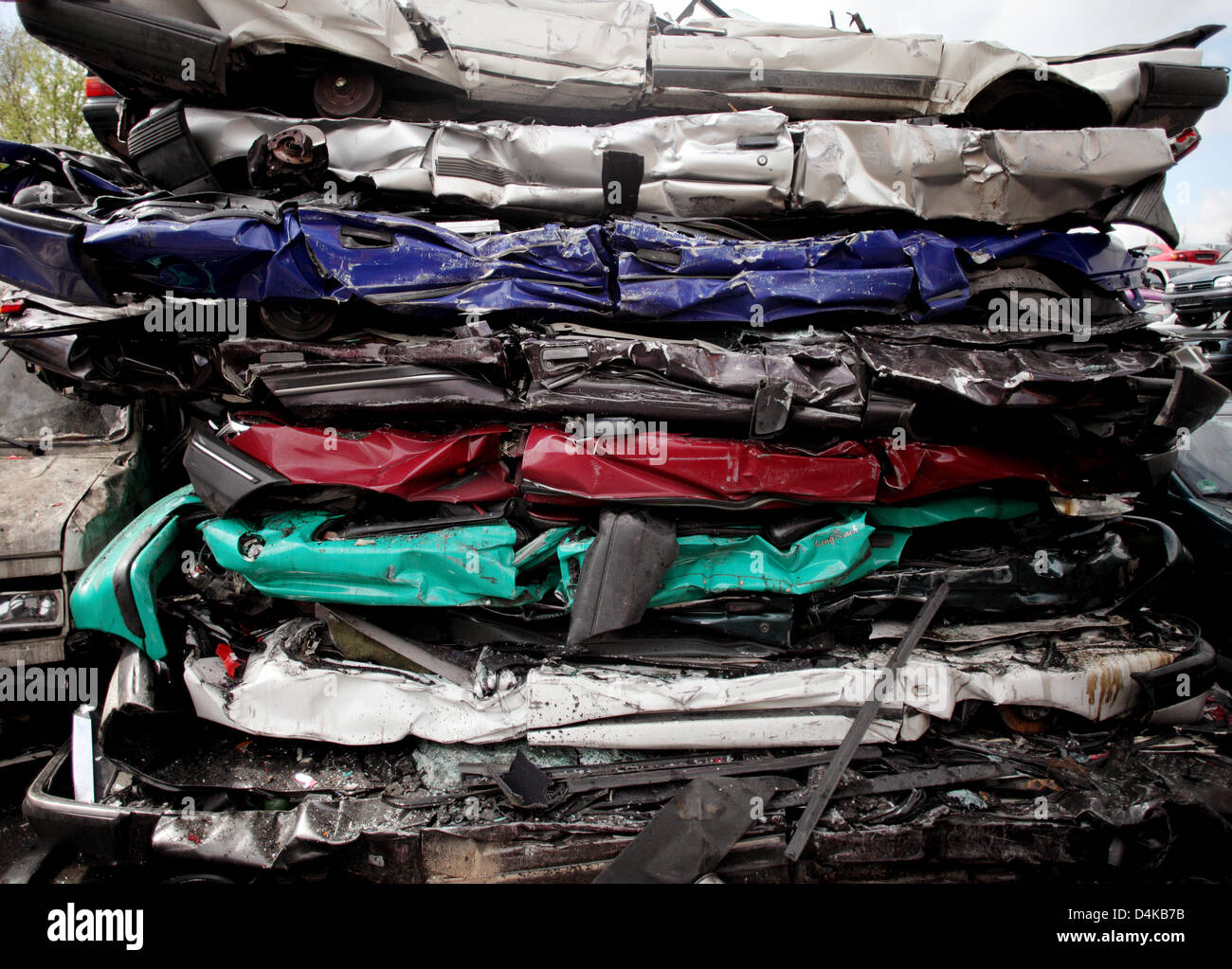 Crushed scrapped cars piled up at a car recycling plant near Stock ...