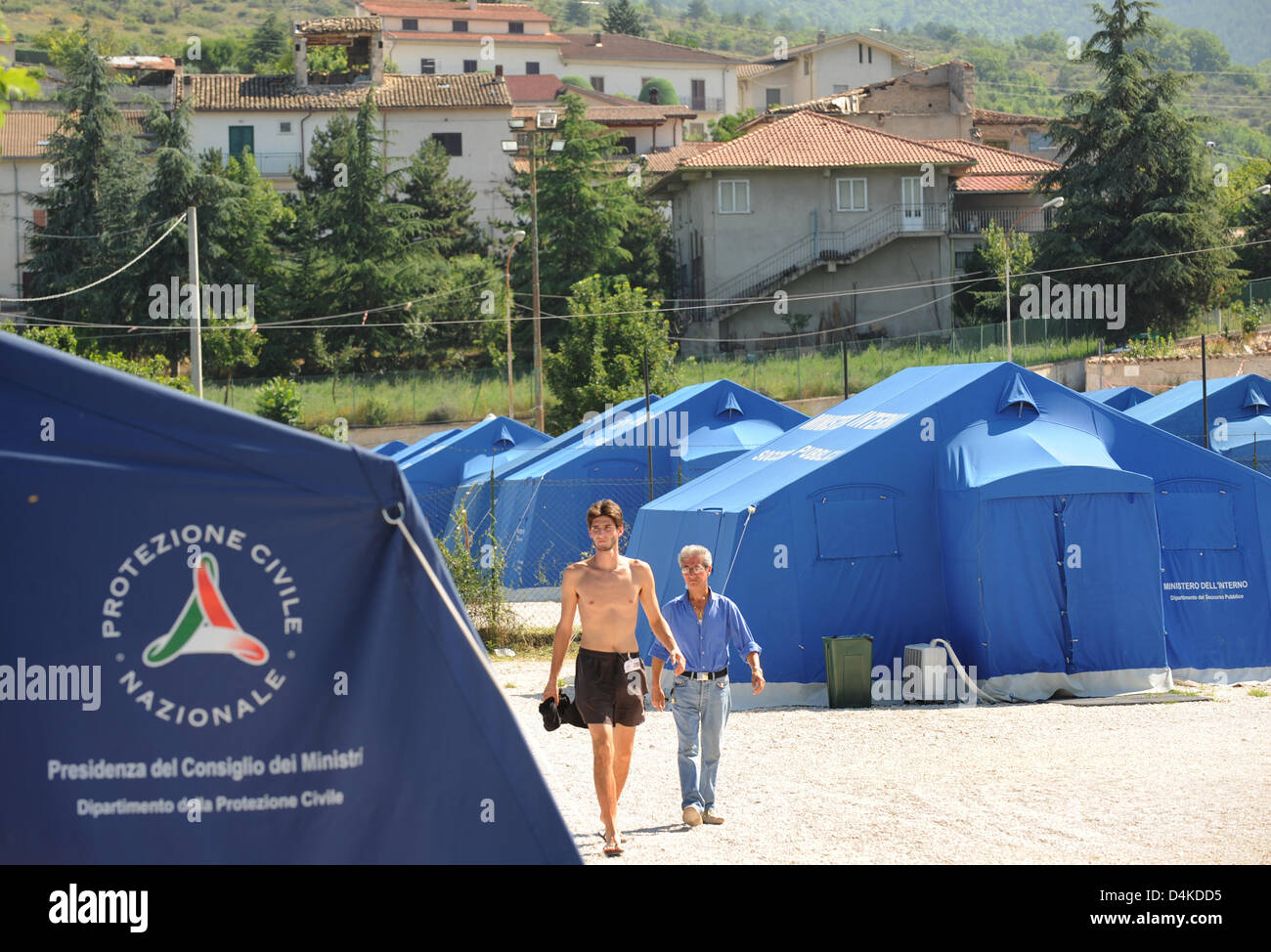 Displaced citizens walk past tents at a refugee c& run by the Red Cross in San Gregorio near L?Aquila Italy 07 July 2009. In April 2009 an earthquake ... & Displaced citizens walk past tents at a refugee camp run by the ...