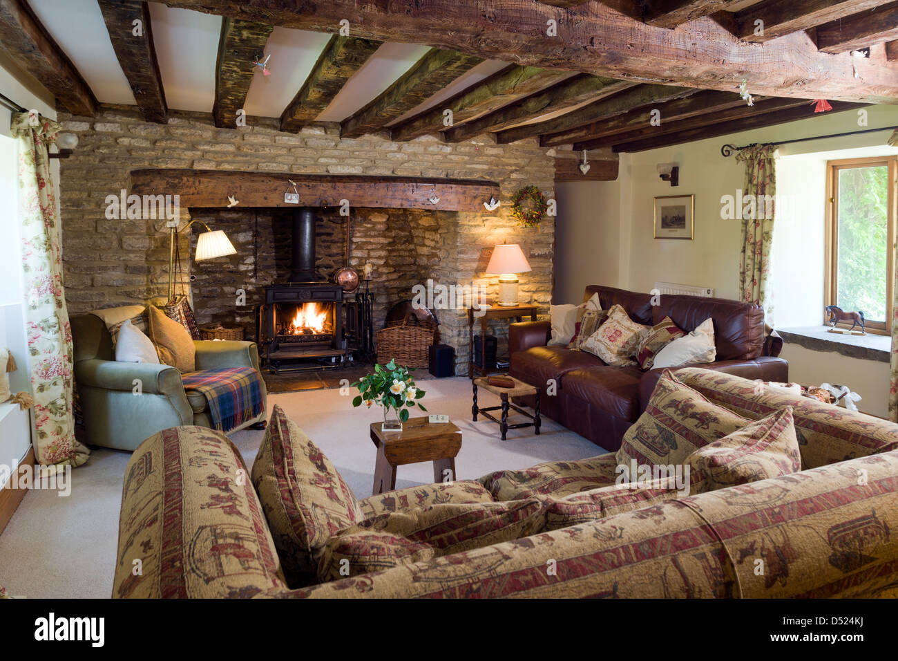 A Cosy Cottage Living Room With A Log Burning Stove Exposed Stone Walls And  Ceiling Beams Features