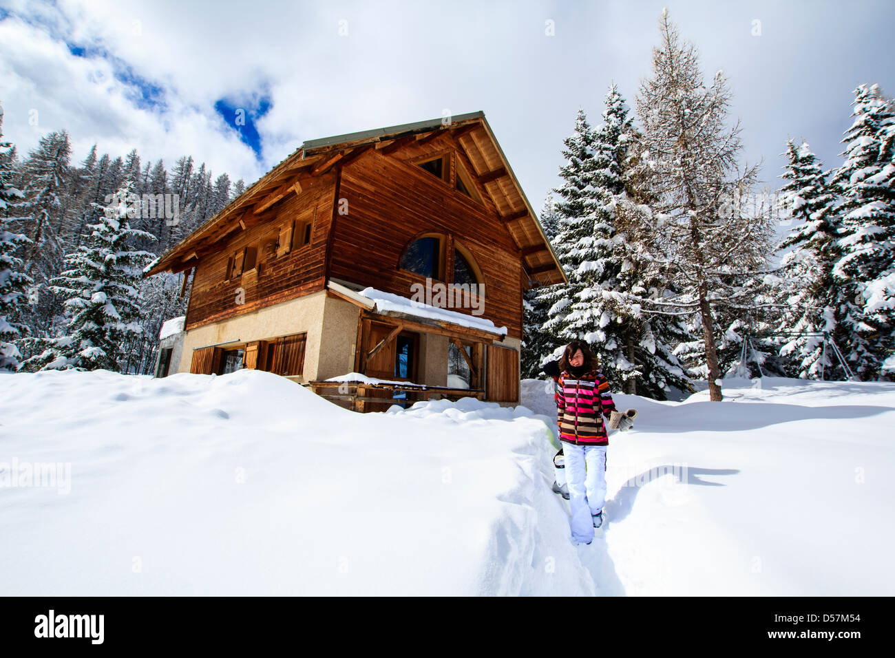 Girl in ski costume walking out of winter ski chalet in French Alps