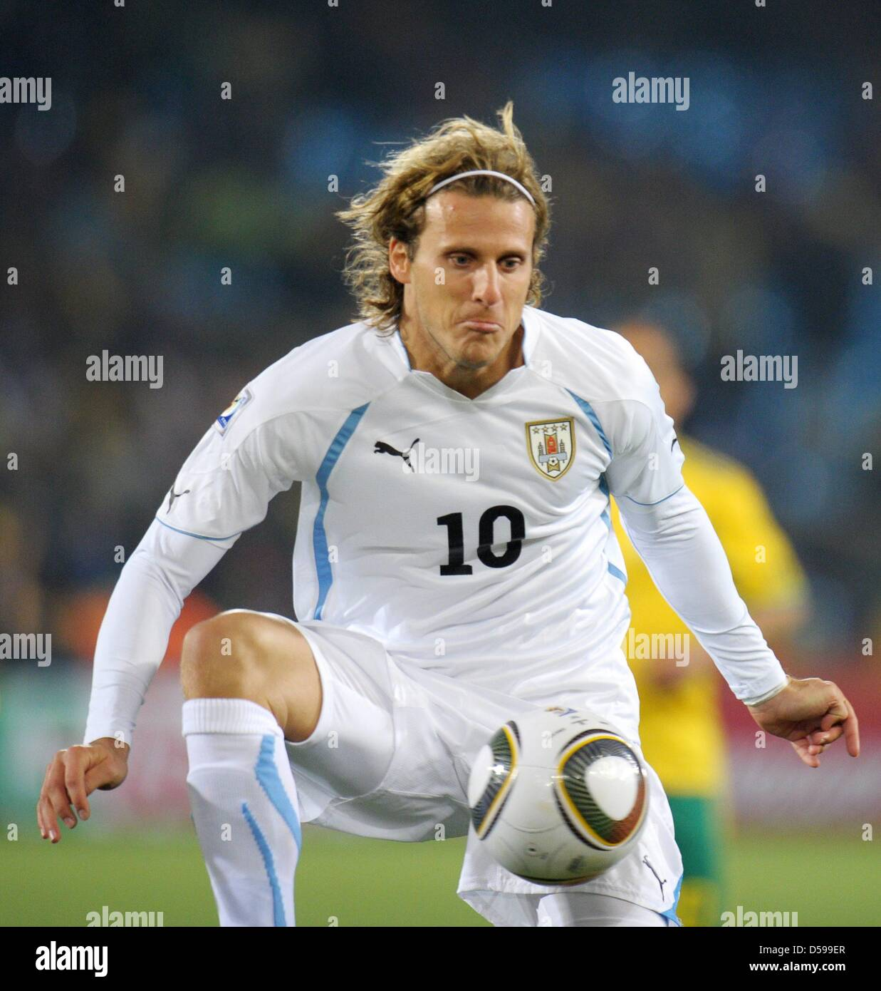 Diego Forlan of Uruguay L controls the ball during the FIFA