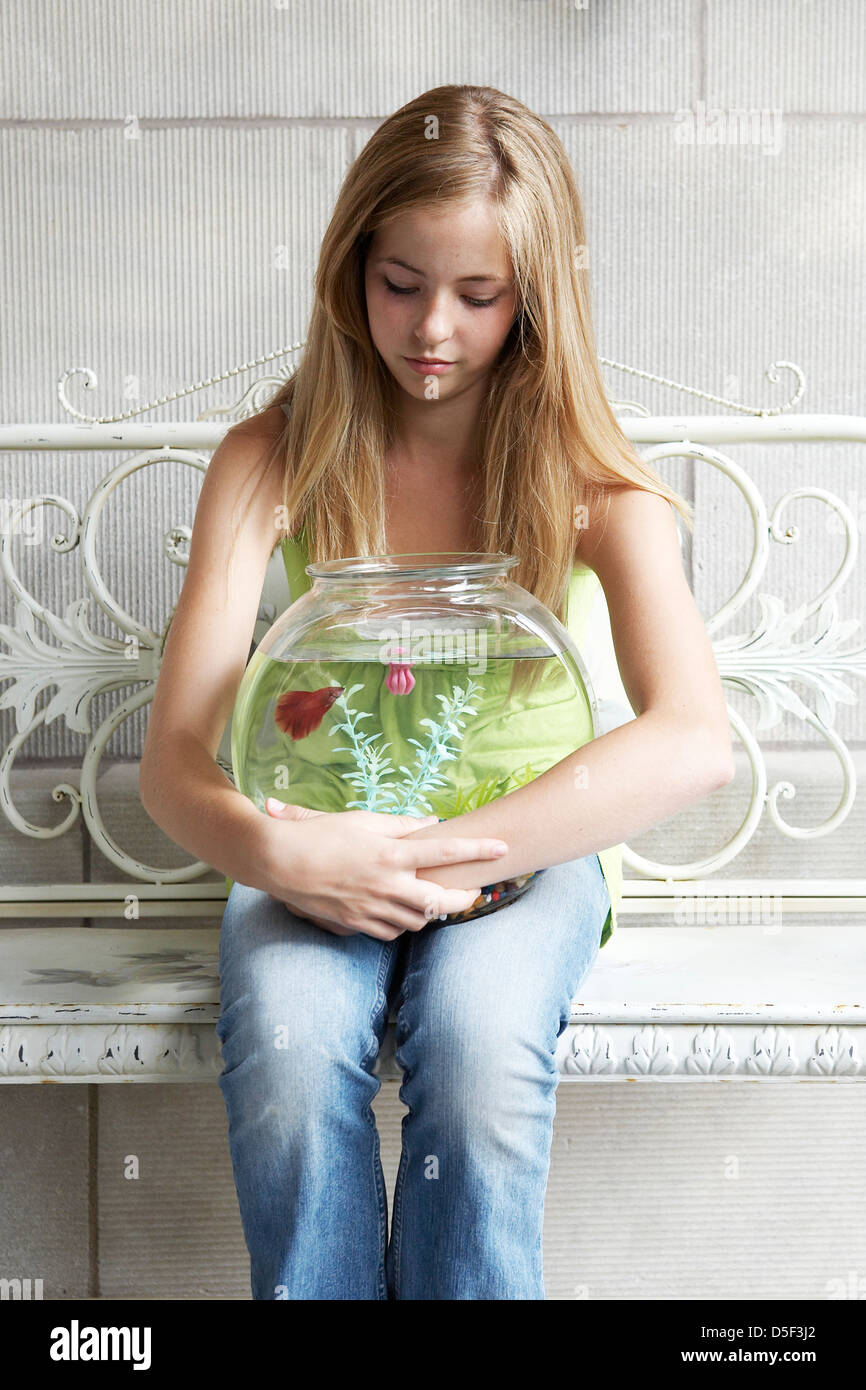 14 year old girl holding fish bowl - Stock Image.