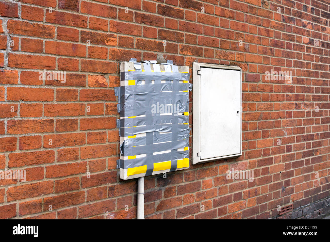 Broken Service Meter Box On Brick Wall Of A House Held Together With Duct Tape