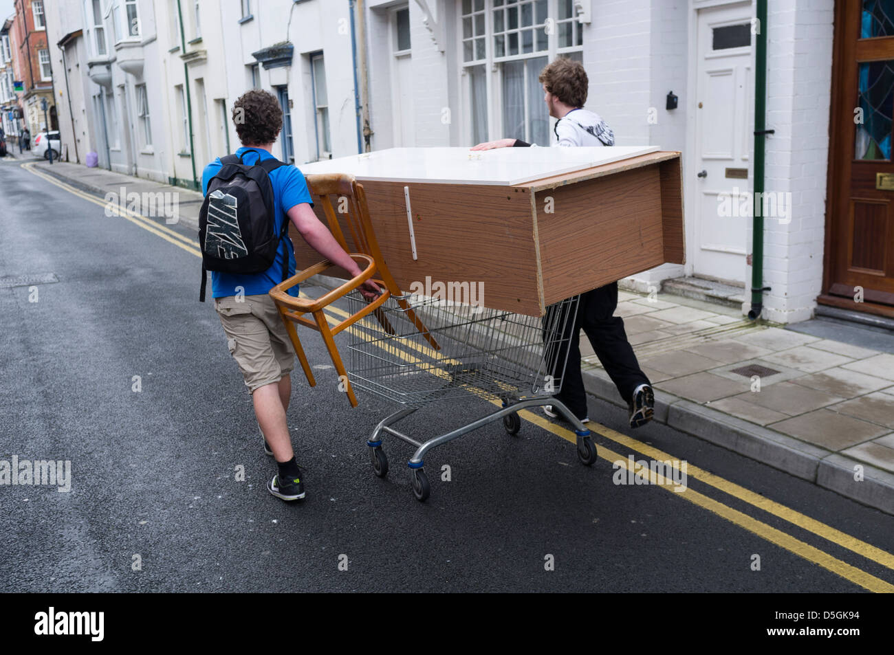 Two Students People Men Moving Furniture Wheeling A Wardrobe On A Shopping  Trolley Aberystwyth Wales Uk