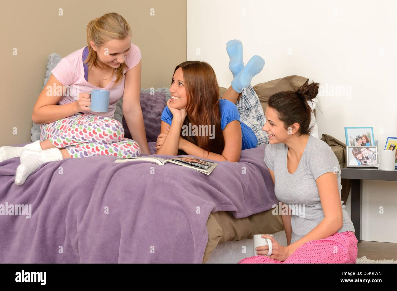 Three Teenage Girls Talking At Pajama Party In Bedroom