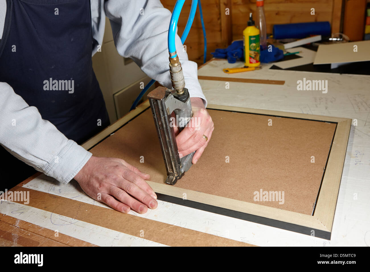 Framer using a v nailer picture frame joiner in a framing workshop framer using air nailer to nail backboard on a picture frame in a framing workshop jeuxipadfo Images