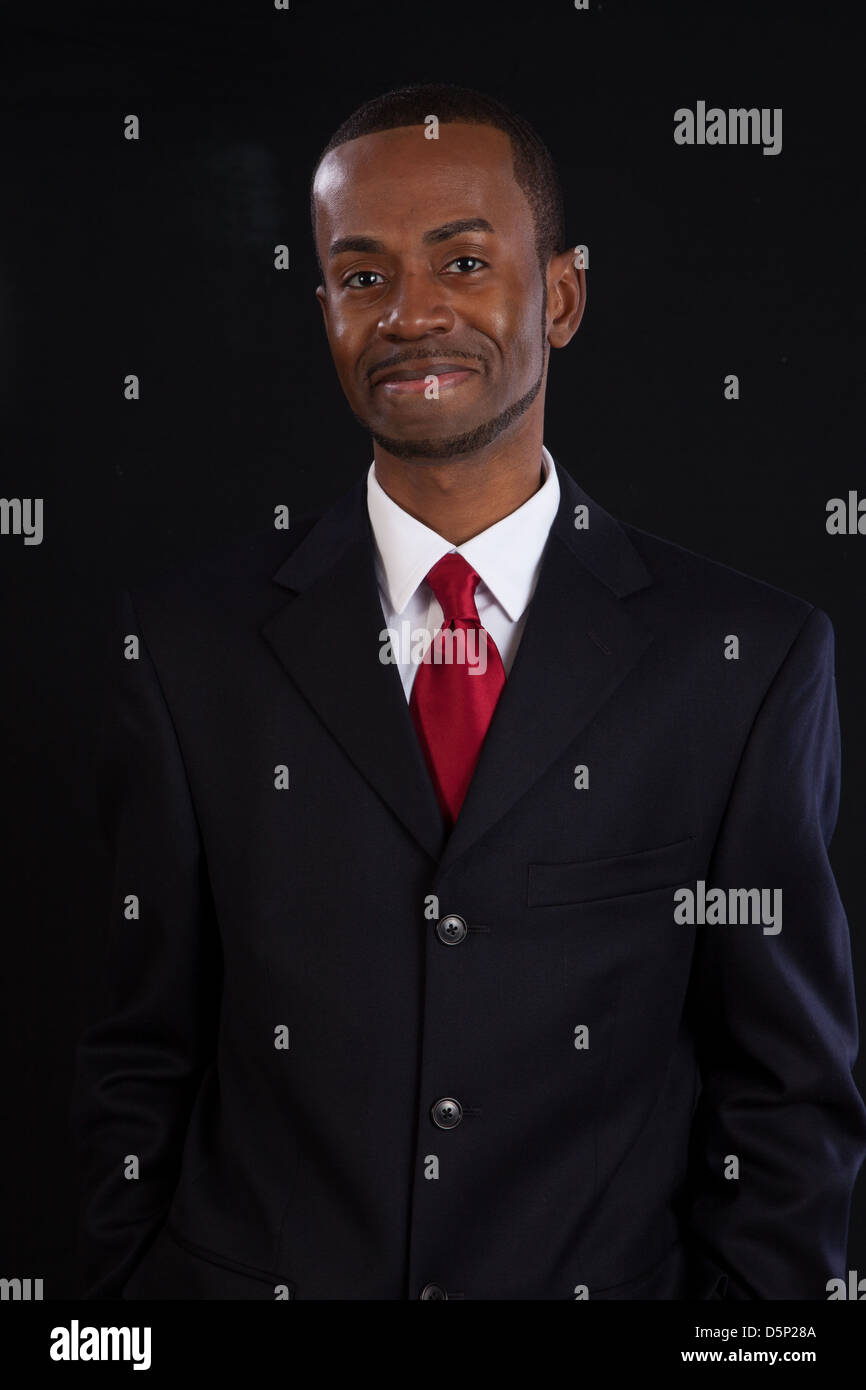 Black man in dark suit, white shirt and red tie, a successful ...