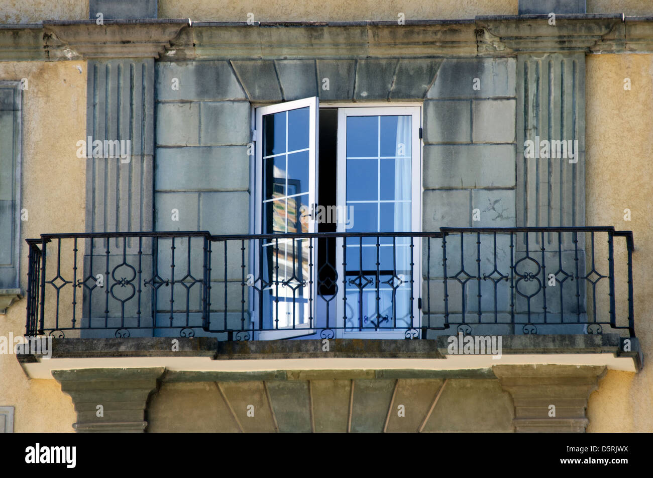 French doors open onto a wrought iron balcony overlooking for Balcony french